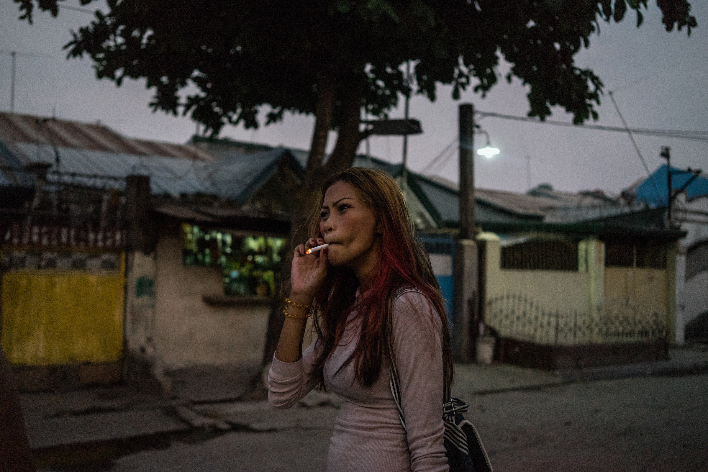 Jojo smokes before a night of work in the bars in Angeles City, known for its red light district. After being displaced from Typhoon Haiyan, Jojo had to go back to work in the red light district shortly after giving birth. In the wake of typhoons, women and girls from areas vulnerable to natural disasters, particularly Eastern Visayas, are driven into the sex trade amidst constant displacement from storms.