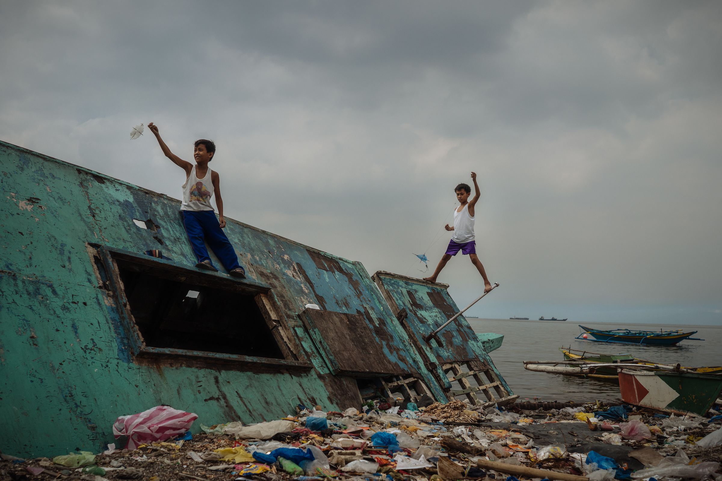Young boys fly kites on an abandoned boat near one of Manila's slums - one of the densest places on earth, and the backdrop of Rodrigo Duterte's War on Drugs. Amidst all the adversity, life goes on for the residents who call this place home.