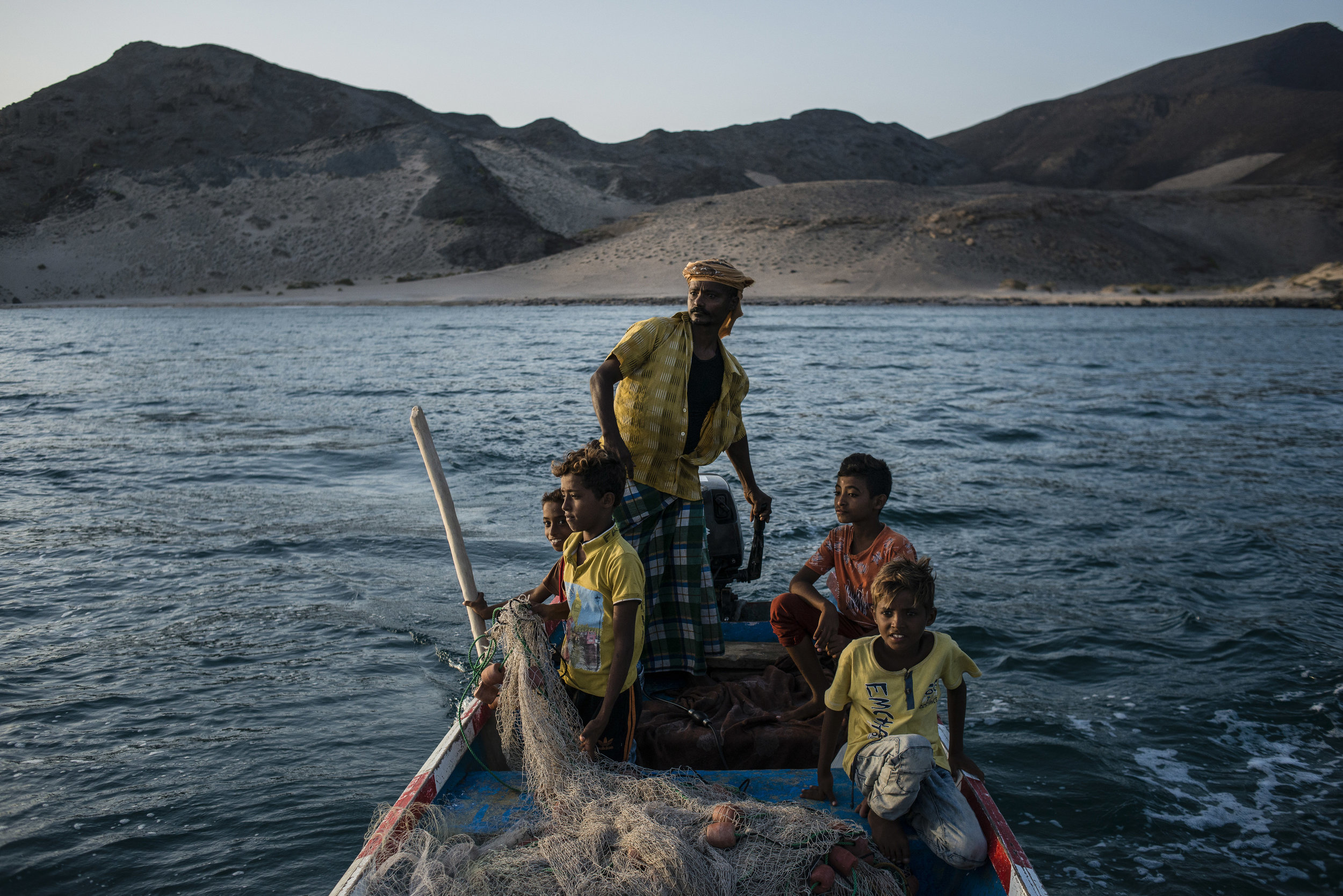"ALEX KAY POTTER  www.alexkaypotter.com  |  @alexkpotter   Shafai (center) drives a boat near the shore in search of schools of fish to catch on May 9, 2018 in Fugum, Yemen. Shafai doesn't send his sons to school: He believes an education won't help them make a living. Instead, he teaches them how to fish. ""Our life and work is on the sea. I can teach my sons the trade, and they can provide for themselves. We're poor in work, but we're rich in life.""  From National Geographic:    As War Rages, Yemen's Fathers and Sons Face an Uncertain Future   ."