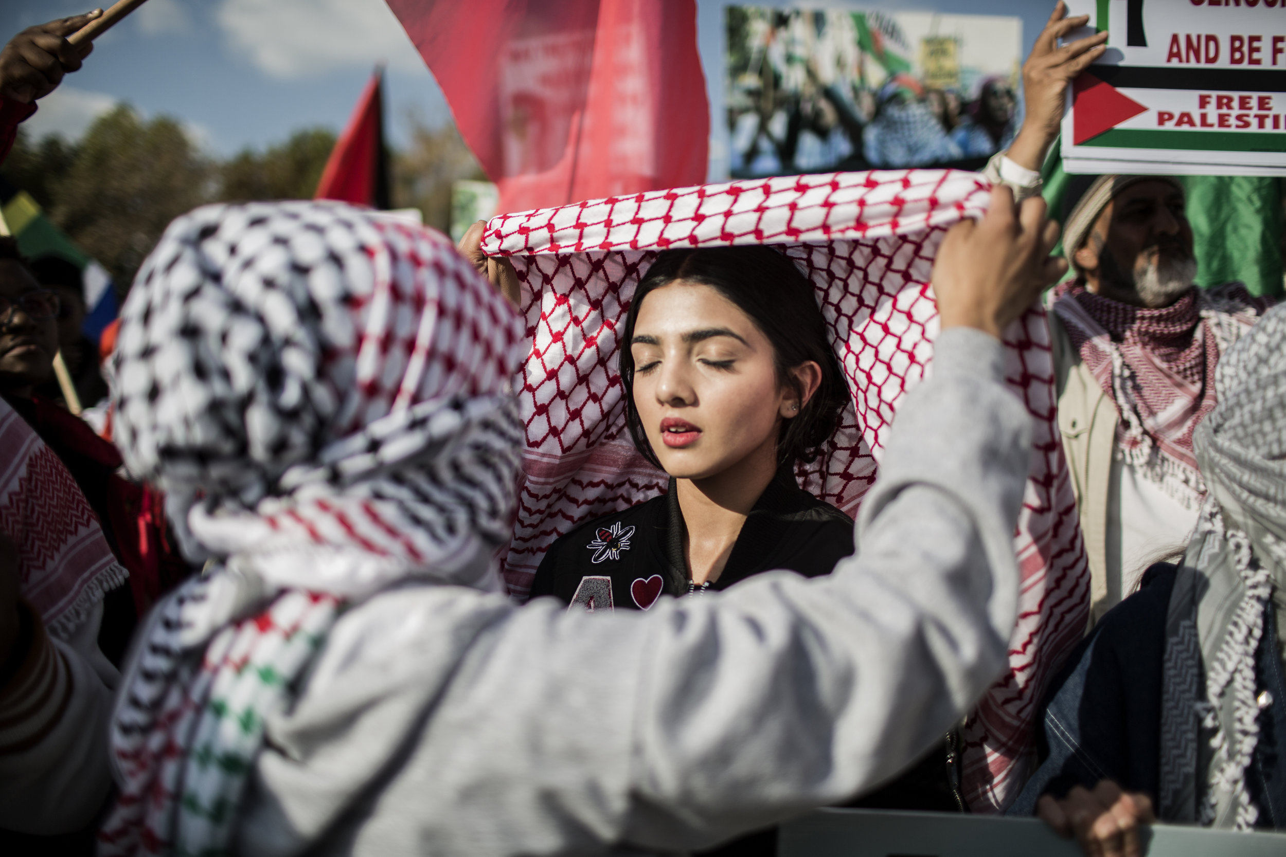 GULSHAN KHAN  gulshankhan.photoshelter.com  |  @gulshanii   A girl ties the Palestinian keffiyeh during a demonstration of members of pro-Palestinian groups and other civil society groups outside the U.S. Consulate General in Johannesburg, South Africa on Tuesday May 15, 2018 to protest against the killing of 59 Palestinians in clashes and protests the day before, coinciding with the United States formally moving its embassy in Israel from Tel Aviv to Jerusalem.