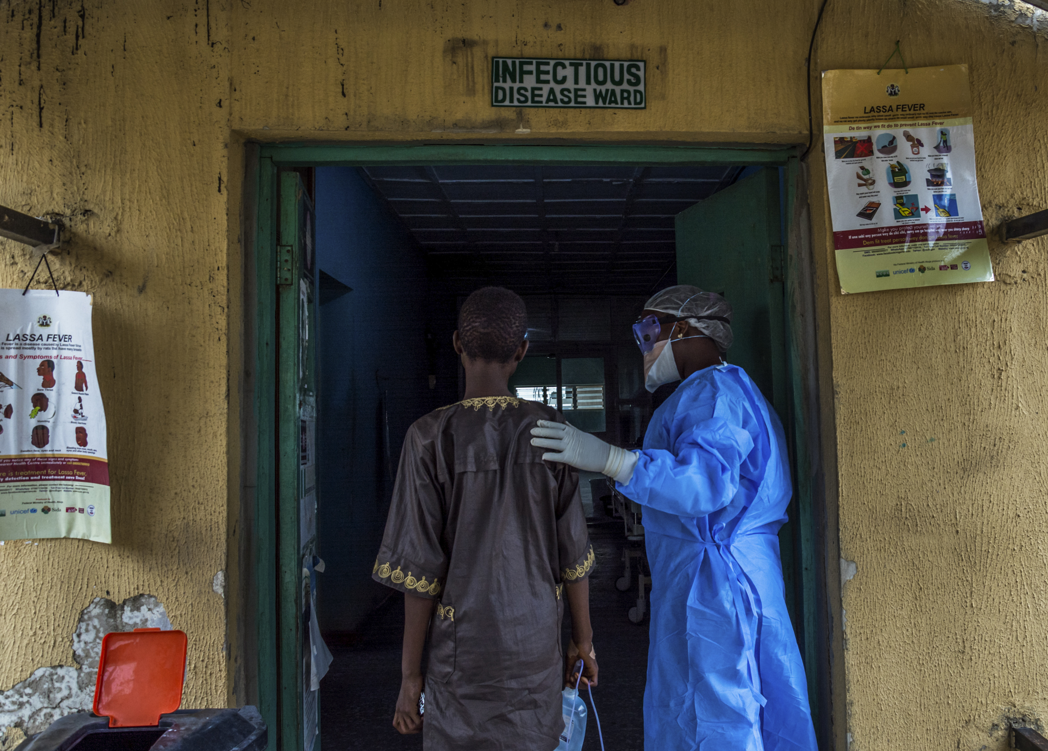 ETINOSA YVONNE  www.etinosayvonne.me  |  @etinosa.yvonne   A nurse accompanies a patient suspected to have Lassa fever to the isolation ward at the Federal Medical Center in Owo, Ondo state, in March 2018. During the first quarter of 2018, Nigeria experienced the worst outbreak of Lassa fever in 49 years. The outbreak led to the death of over a 100 people in different parts of the country.