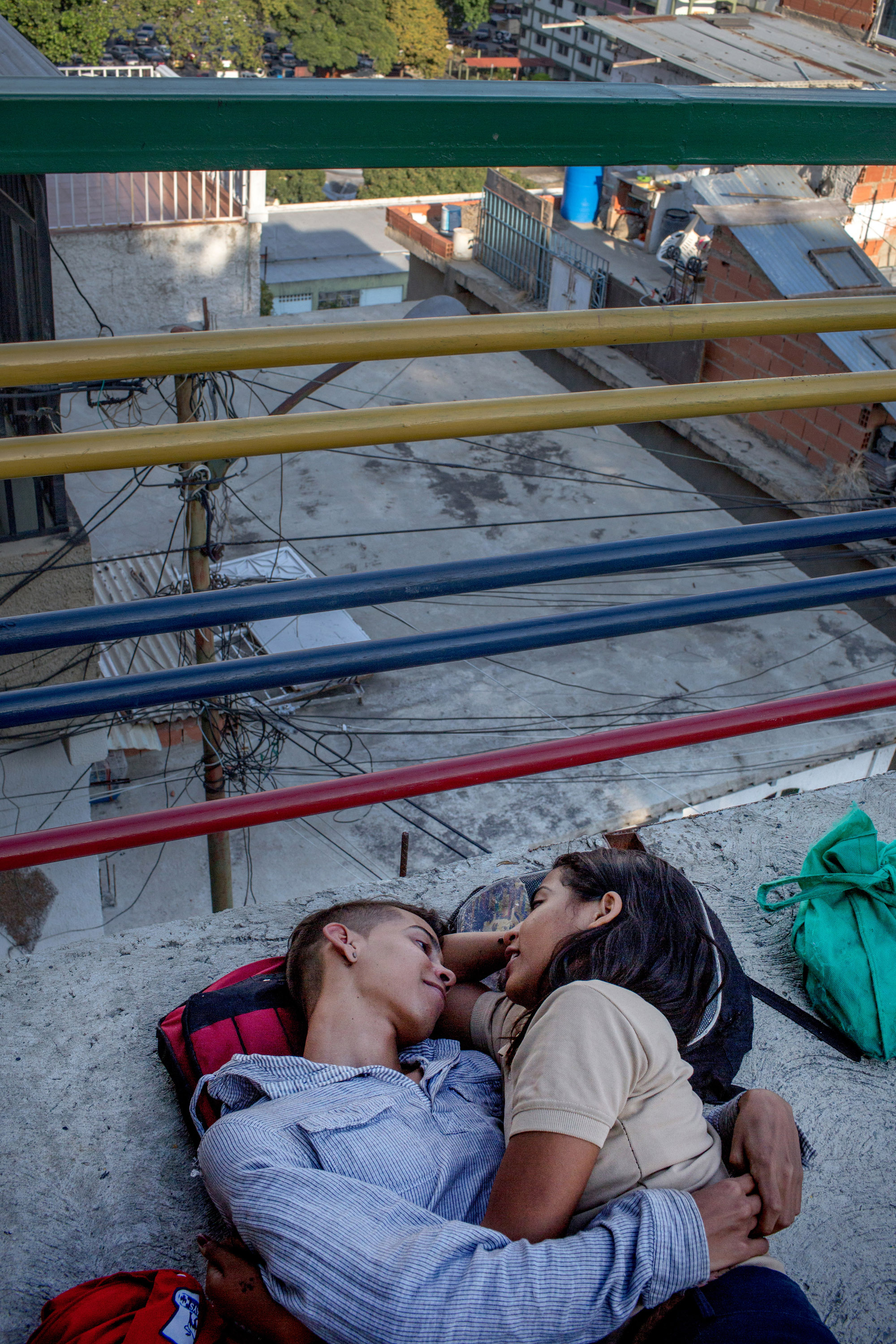 Javier and Solimar, a young couple, embrace after school in the neighborhood of El 23 de Enero in Caracas. Amid a severe economic and political crisis, thousands of young, creative and ambitious Venezuelans are fleeing in search of more opportunity, less violence, and a stable economy. Despite the obstacles, some stay and try to make it in Caracas, many for a variety of reasons cannot leave, others have chosen not to flee.  From The New York Times:    Those Who Stay