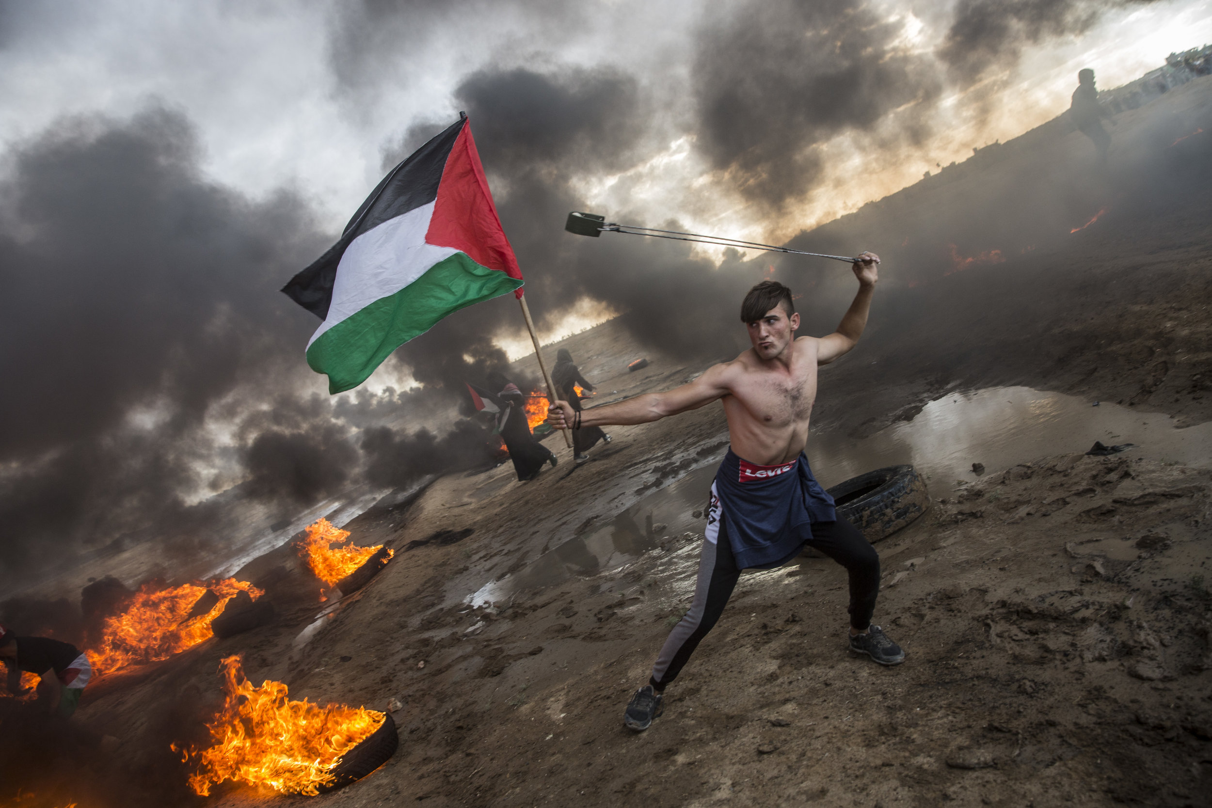 HEIDI LEVINE  heidilevine.photoshelter.com  |  @heidi_levine   Tires burn as Palestinians protestors used sling shots to hurl stones towards Israeli troops along the border of Gaza and Israel east of Gaza City on October 26,2018. Four Palestinians were killed by Israeli military fire during protests at the Gaza-Israel border, Palestinian authorities said. Israeli army helicopters and fighter jets meanwhile attacked three Hamas positions in the northern Gaza strip.