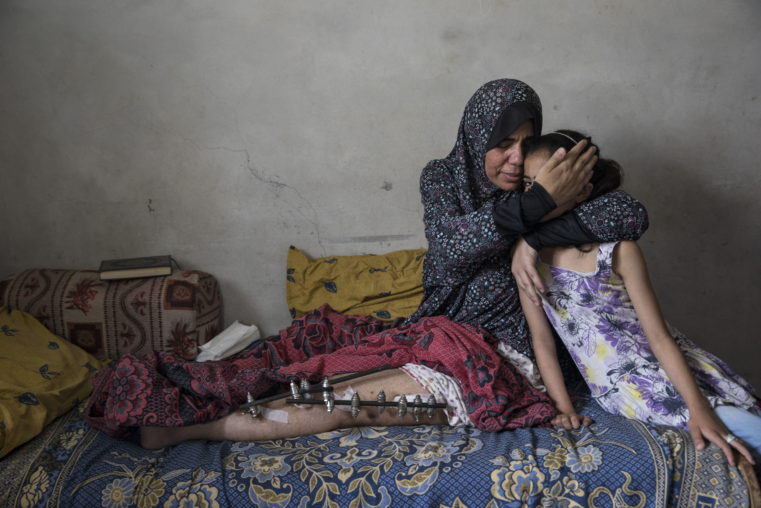 PAULA BRONSTEIN  www.paulaphoto.com  |  @pbbphoto   Kefah Al-Ajrami, 47, holds her daughter Zamzam Al-Ajrami, 9, who was crying after seeing her mother in pain on May 22,2018 in Gaza City. Kefah is a mother of seven, she was shot in her left leg with an exploding bullet causing extensive injury to her leg. She went to the protests on March 30th along with her children and husband, when the Israeli military (IDF) started using new weaponry, explosive bullets meant to shatter bones and destroy veins and arteries.