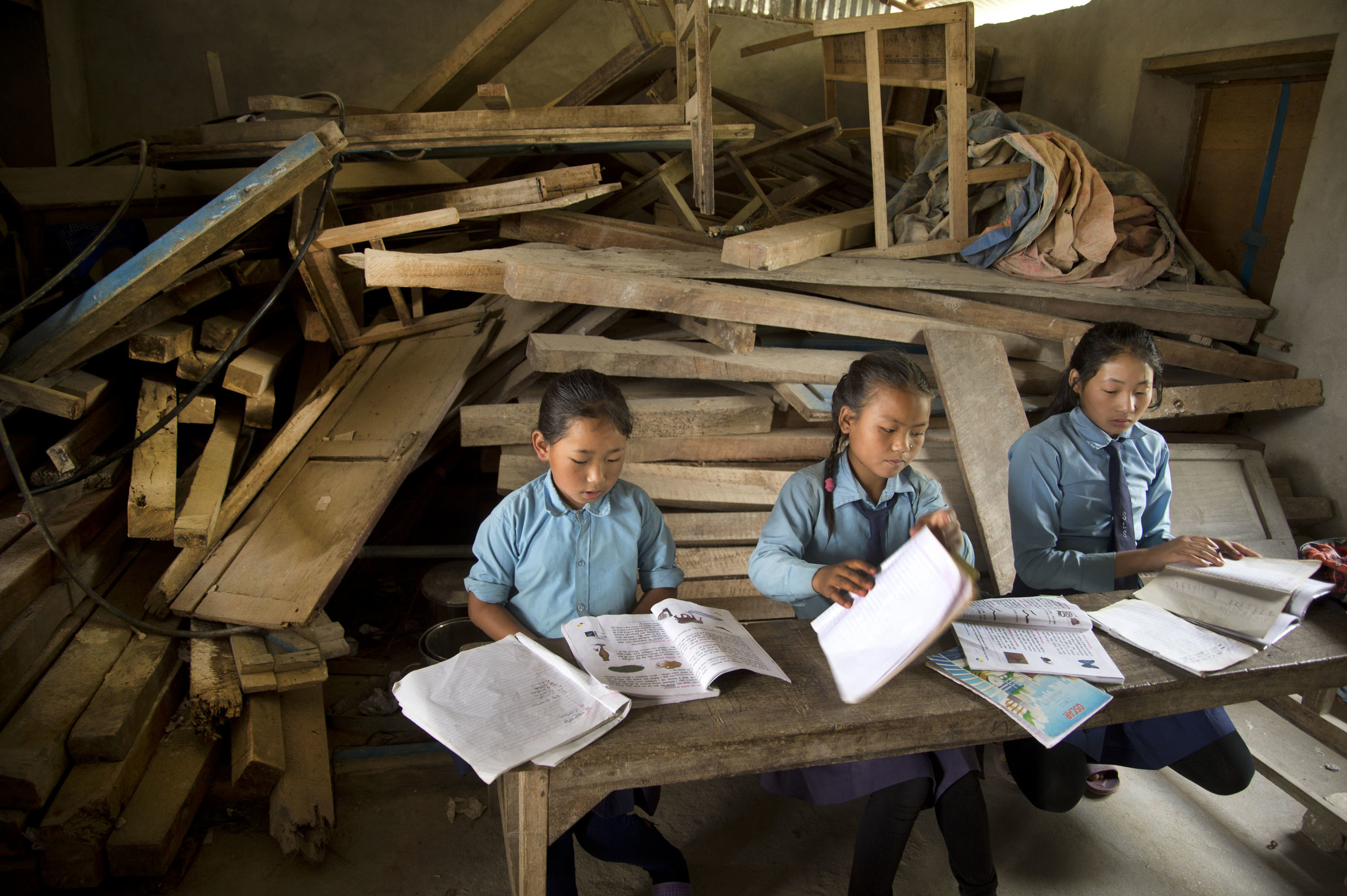 JENNY MATTHEWS  jennymatthews.photoshelter.com  |  @jennymphoto   Nepalese schoolgirls study in a classroom in Pangma village that was damaged by the 2015 earthquake and hasn't been repaired.