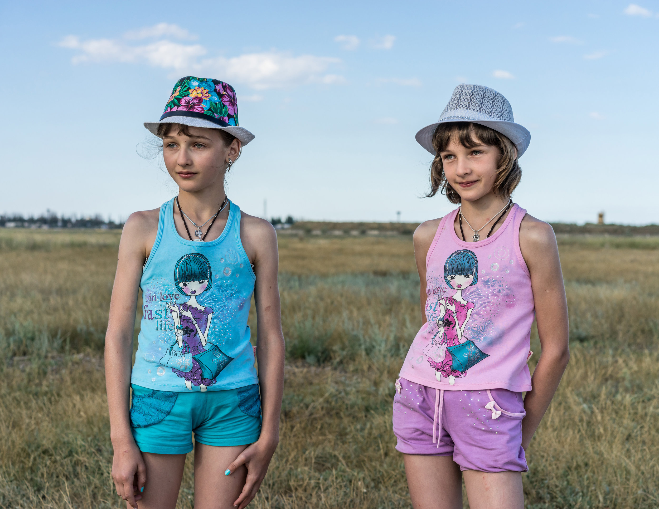 OKSANA PARAFENIUK  www.oksanaparafeniuk.com  |  @oksana_par   Twin sisters Tania, left, and Olia, 11 years old, from the Khmelnytskyi region in Ukraine pose for a portrait while on vacation near the salt lake on Arabat Spit on July 2, 2018. The Arabat Spit is a narrow strip of land which separates a system of lagoons named Syvash from the Sea of Azov.