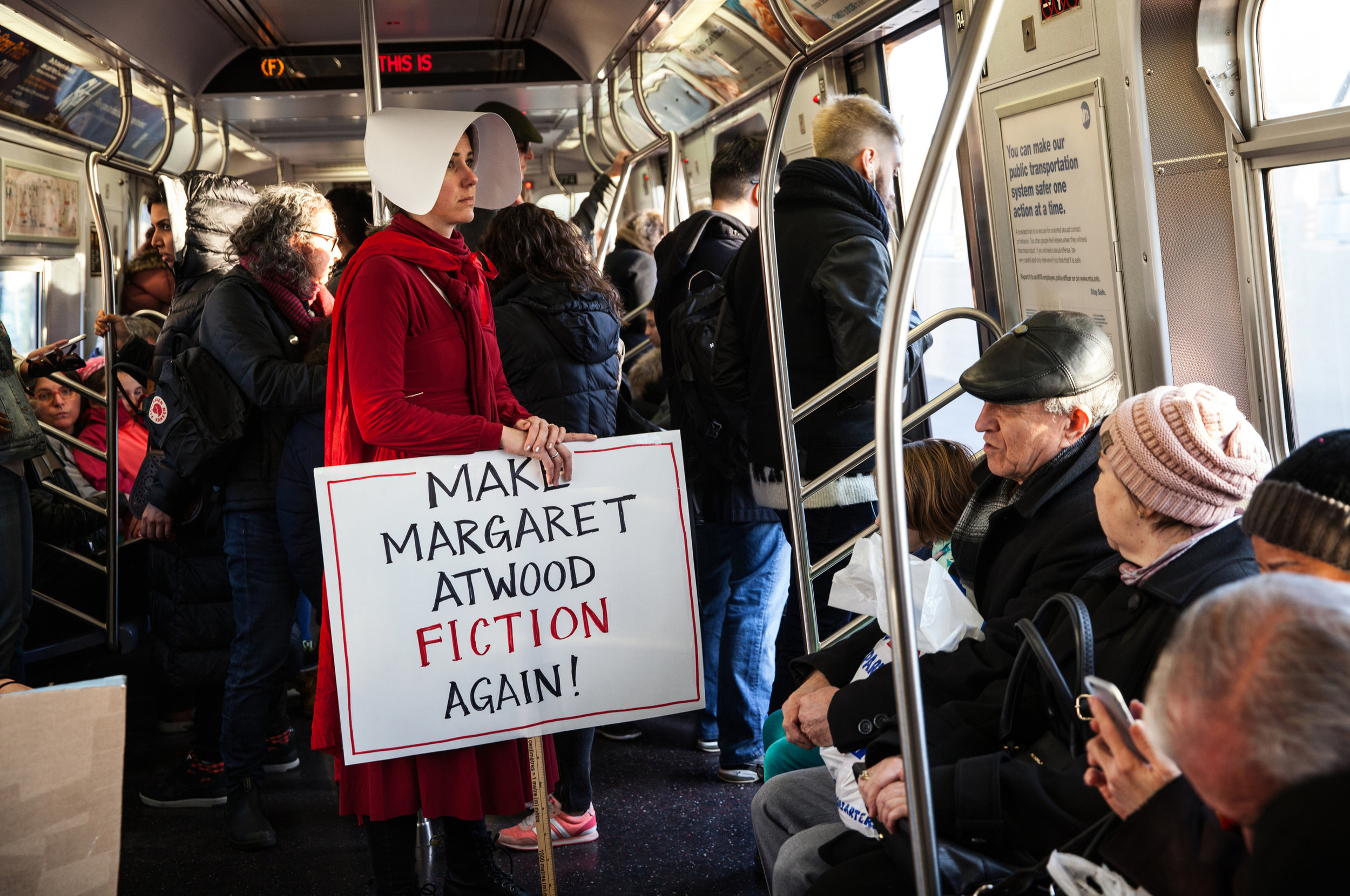 "HOLLY PICKETT  www.hollypickett.com  |  @hollypickettpix   A woman dressed as a fictional character from Margaret Atwood's ""The Handmaid's Tale"" rides the subway after the Women's March in Manhattan, NY, on January 20, 2018."