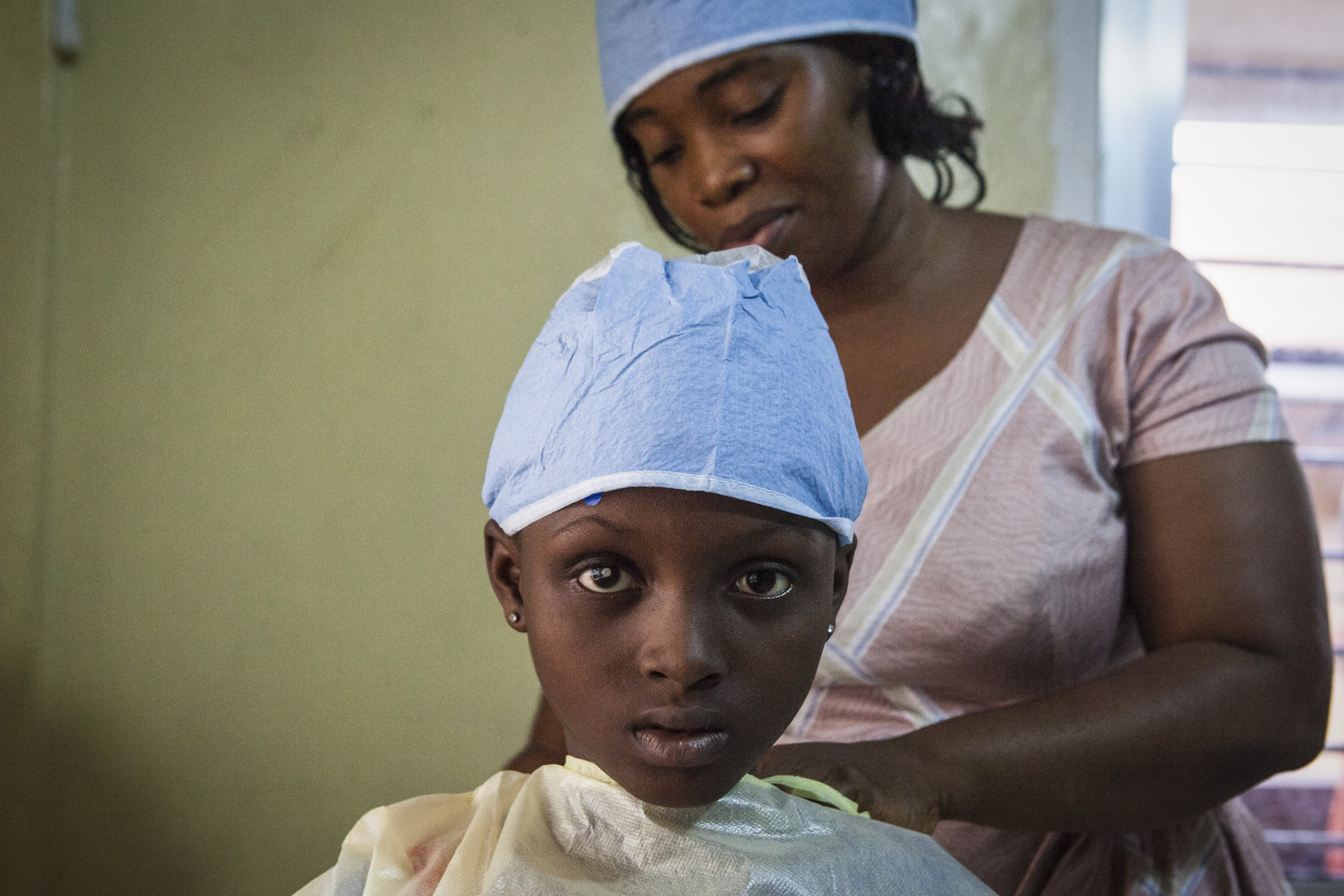 Aminata Conteh, 8, puts on a hospital gown before doctors remove fluid from her problematic right eye for testing at the Kissy United Methodist Church Eye Hospital in Freetown, Sierra Leone. Long after recovering from the largest Ebola outbreak in history, survivors continue to experience debilitating complications including uvetis, an inflammation of the eye, leading to severe cataracts leaving the survivor with little to no sight in the affected eye.