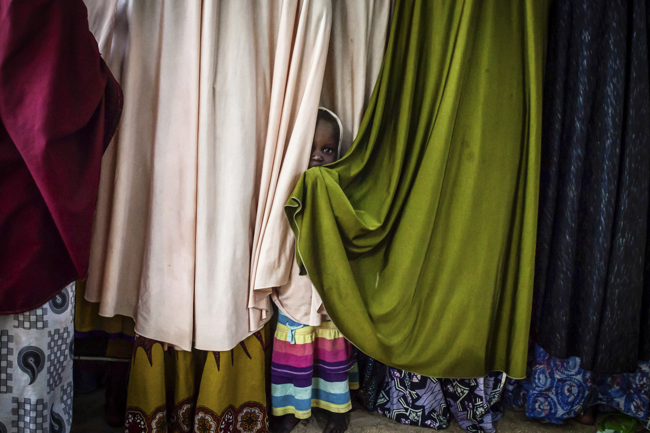 """The daughter of a former Boko Haram commander plays between the chadors of their wives at a """"safe house"""" in Maiduguri, Nigeria."""