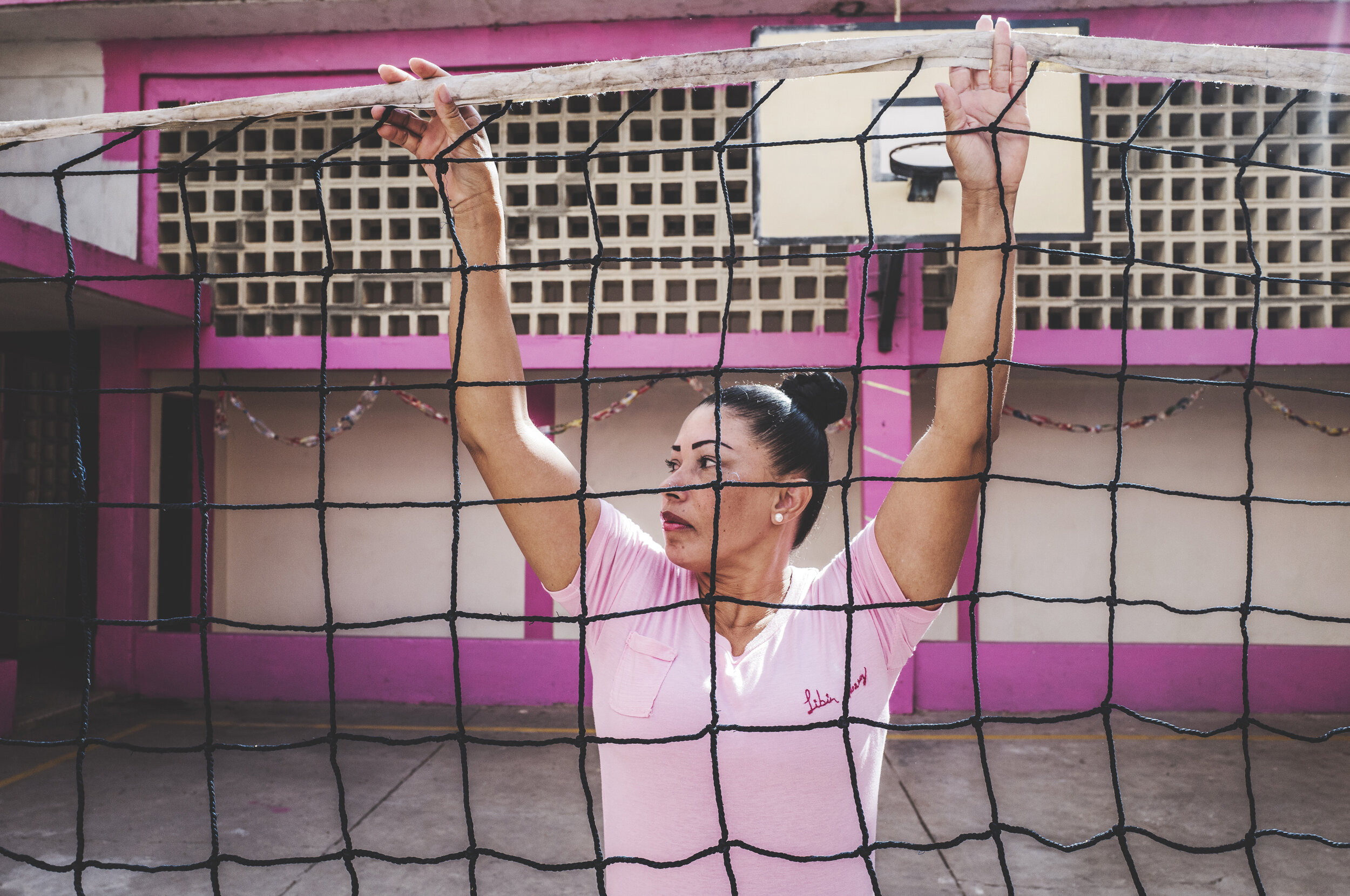 "A woman inside a ""closed"" prison in Maracaibo - the border city between Venezuela and Colombia - helps arrange the net to play volleyball."