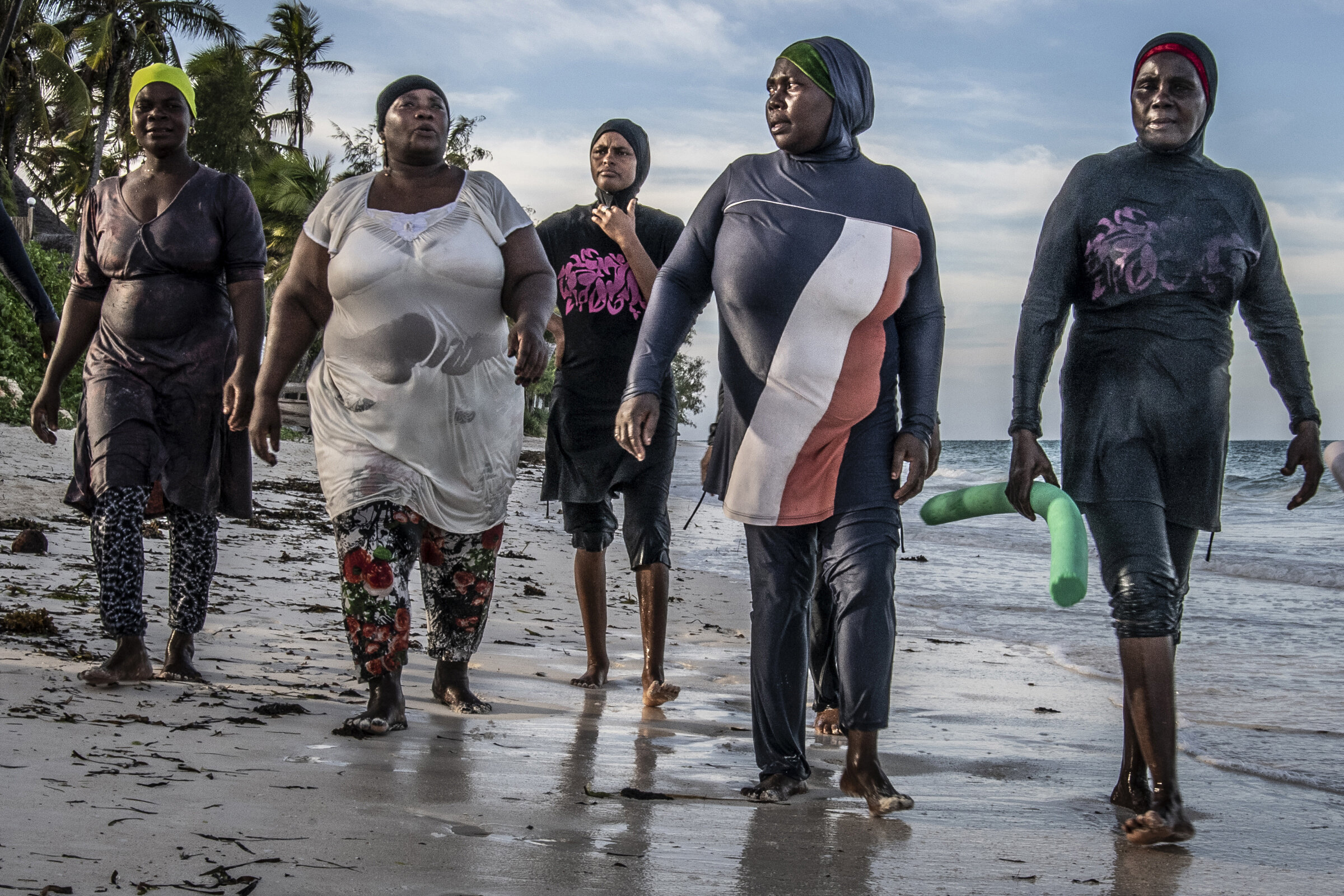 Swim instructor, octopus hunter, elder Bisichana (far right) walks on shore with her octopus hunter swim students after their lesson. Second from left is the wife of the village elder.