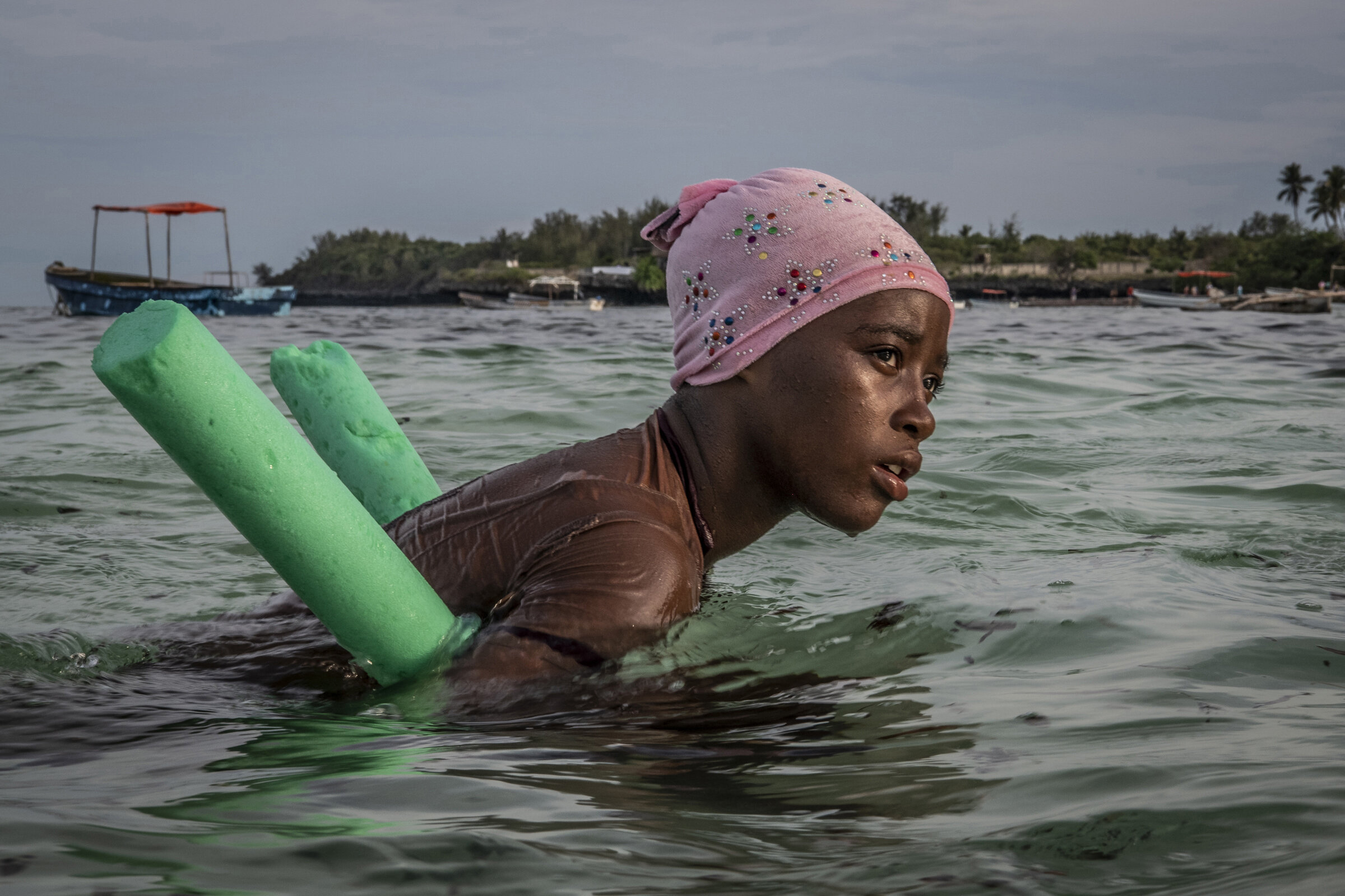 A student rests in shallow water after her swim lesson.