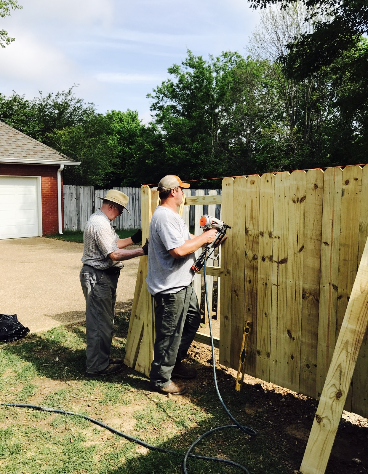 David and Allan Smith fixing the fence and cleaning up the yard.
