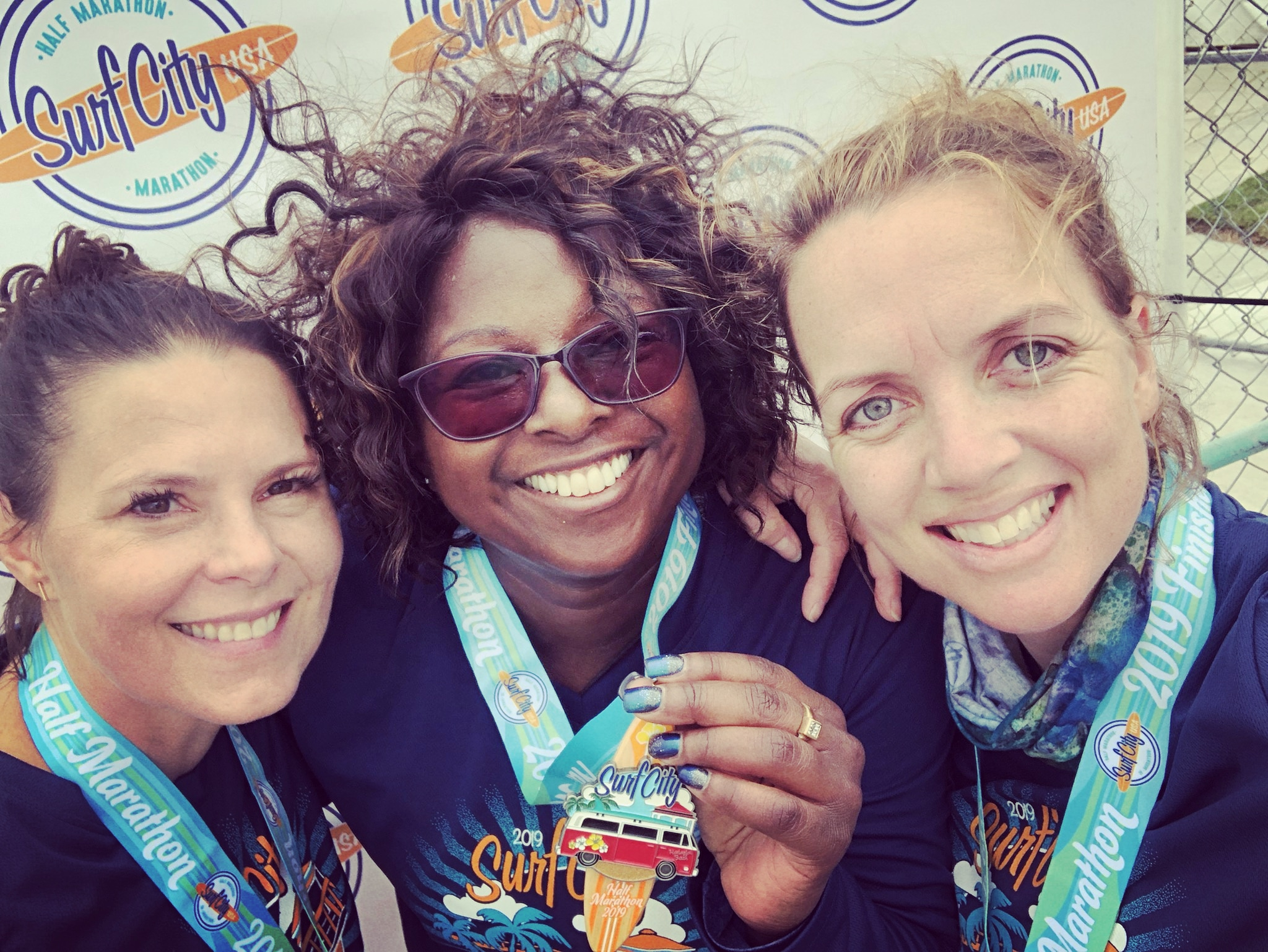 Melissa Mueller (left) and Deb Johnston (right) hold up their first half-marathon medals with Rahbin Shyne.
