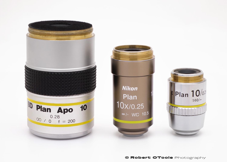 Nikon CFI Plan 10X Achromat next to the massive Mitutoyo BD Plan APO 10X and Nikon E Plan 10X.