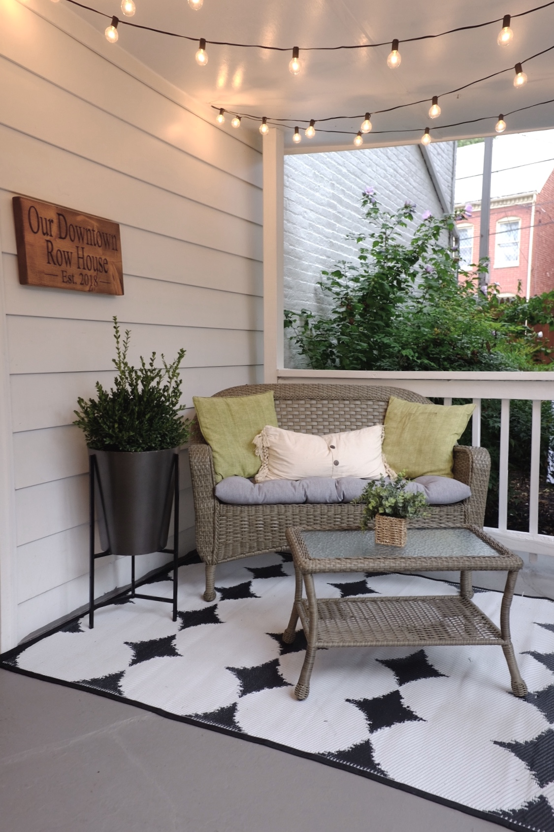 We added lights and a wicker couch so our guests can enjoy the backyard.  Rowhouse sign is from  Smith Crafted Wood Works .
