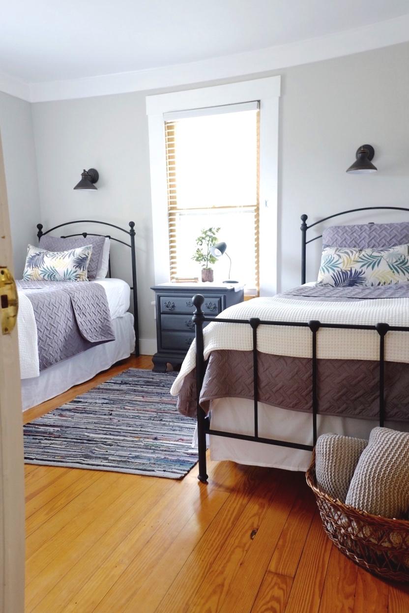 Blue Rag Rug  -  Black Iron Bed  -  White Waffle Coverlet  -  Gray Coverlet