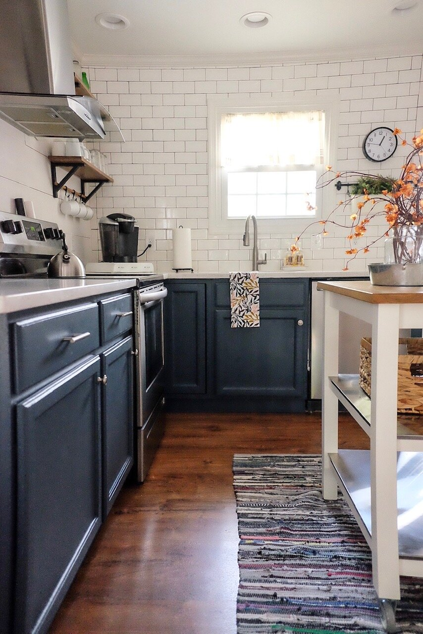 These navy cabinets in the  Bungalow Airbnb  make the orange Fall blooms stand out!