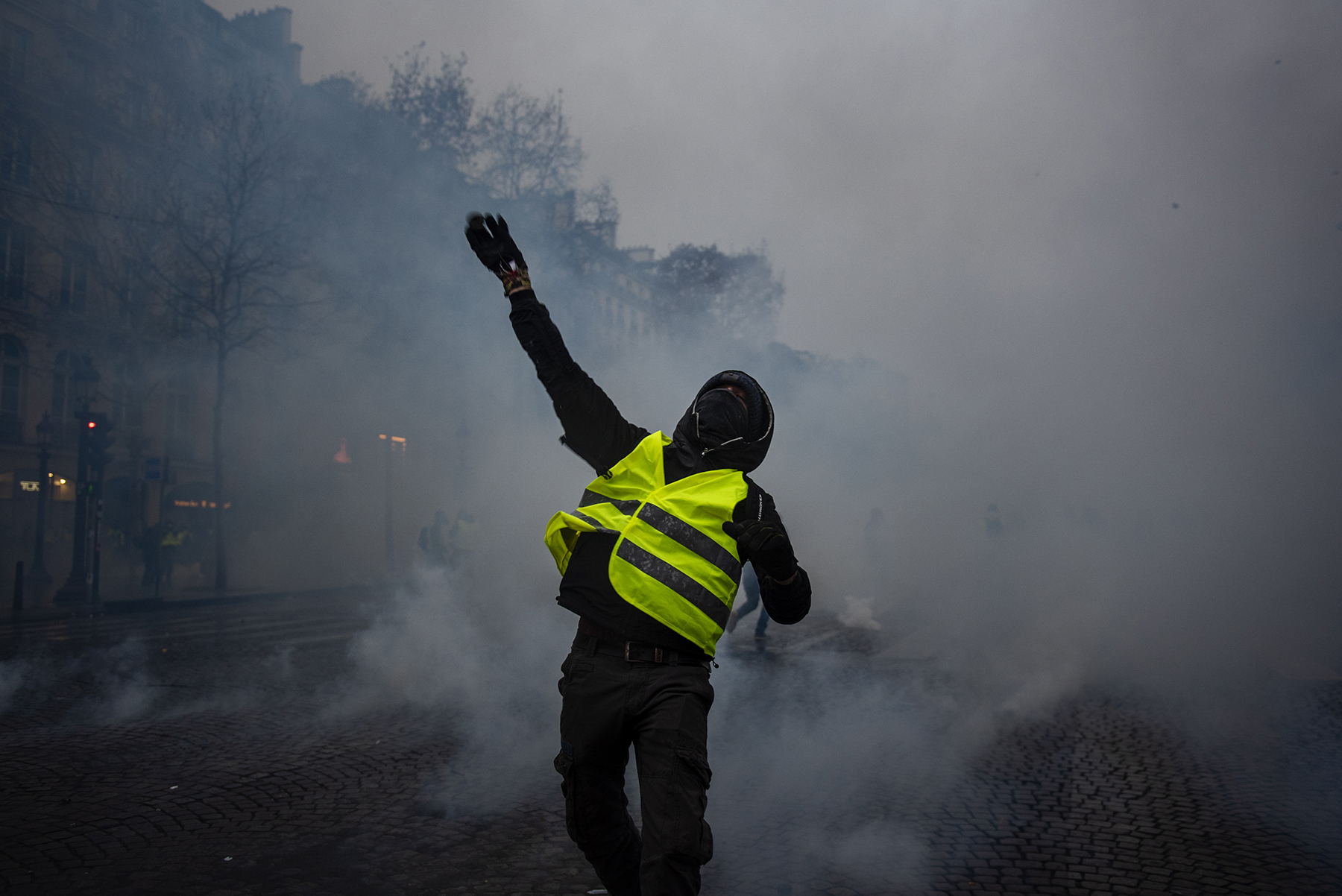A 'Gilets Jaunes' ('Yellow Vest') protester throw a tear gas canister back at French riot police during a demonstration in the Champs Elysees Avenue in Paris, France, on December 15, 2018. Despite French government ministers appeals to the nationwide 'Gilets Jaunes' ('Yellow Vest') protests to stop in the wake of the Strasbourg attack that killed three people on December 11, protesters took the streets of France for the fifth consecutive Saturday. The 'Gilets Jaunes' ('Yellow Vest') movement - began on November 17, 2018 and inspired by opposition to a new fuel tax - has absorbed a wide range of anti-government sentiment and wrecked Paris and other French cities for over a month.