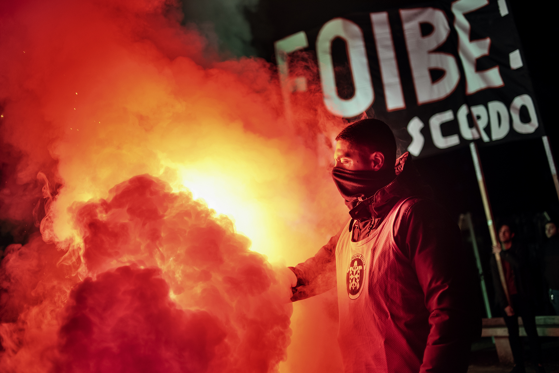 """A supporter of Italian far-right party CasaPound lights up a smoke bomb in front of a banner reading """"Foibe - I don't forget"""" during the National Memorial Day of the Foibe, which remember the victims of the so called foibe massacres, in Rome, Italy, on February 09, 2019."""