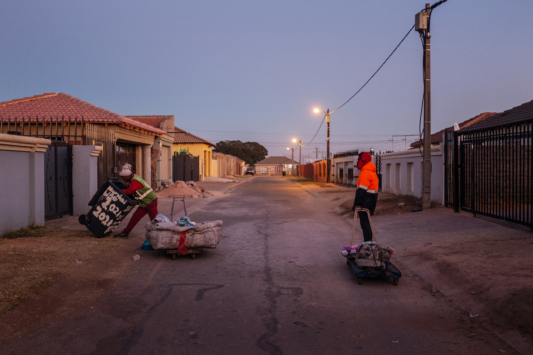 Scelo Sithole, 38, speaks with Tumelo Ikaneng, 21, while they collect waste from trash bins in the streets of Johannebsurg, South Africa in the early morning of June 12, 2019.
