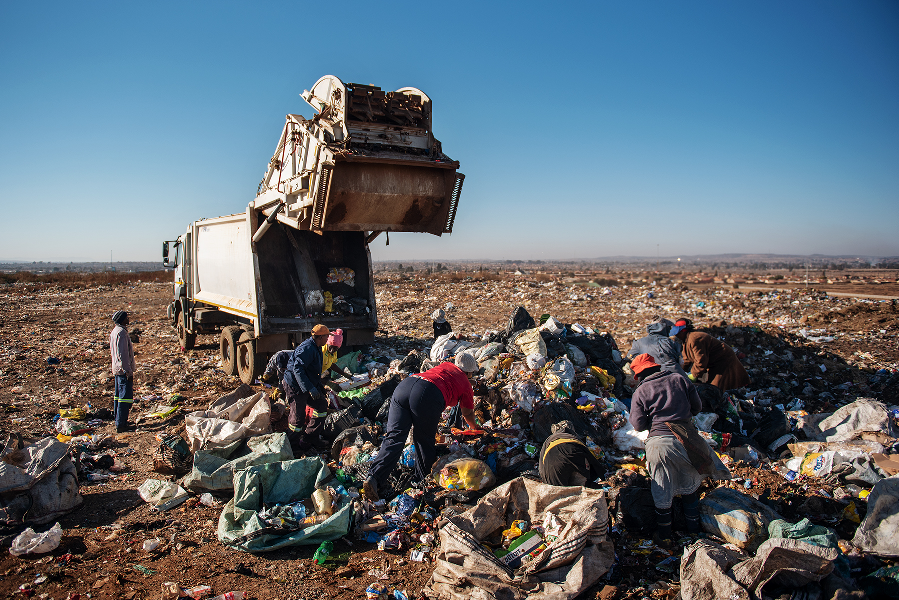 Eva Mokoena, a 33 years old South African informal waste picker, scavenges waste dumped by a garbage truck along with other women reclaimers at the Palm Springs landfill in the outskirt of Johannesburg, South Africa, on June 28, 2019.