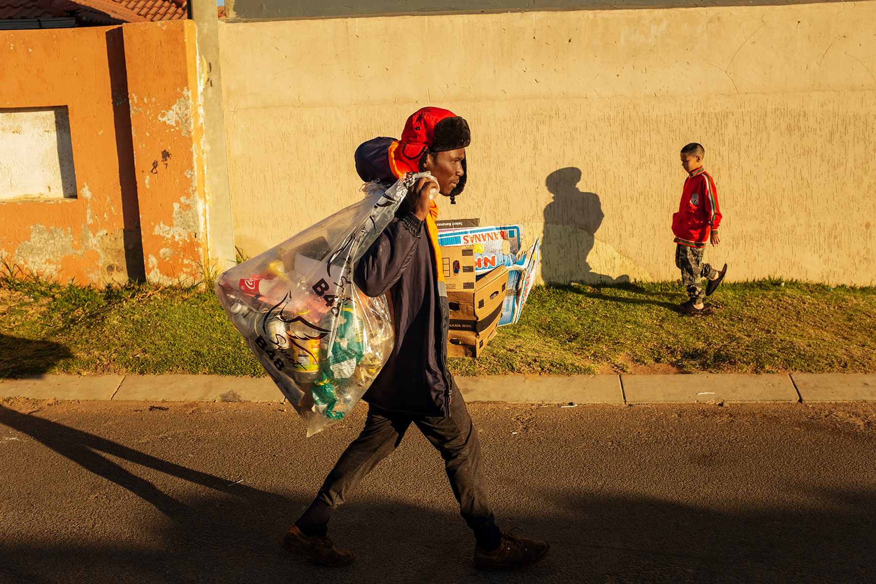 Scelo Sithole, 38, walks carrying bags of collected waste in Johannebsurg, South Africa, in the early morning of June 12, 2019.