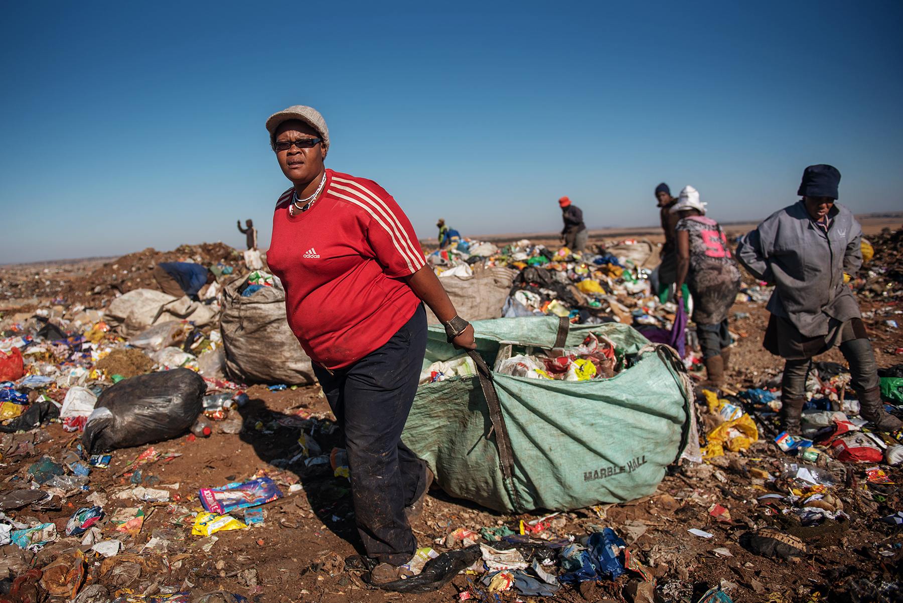 Eva Mokoena (L), a 33 years old South African informal waste picker, drags a sack filled up of waste dumped by a garbage truck at the Palm Springs landfill in the outskirt of Johannesburg, South Africa, on June 28, 2019.