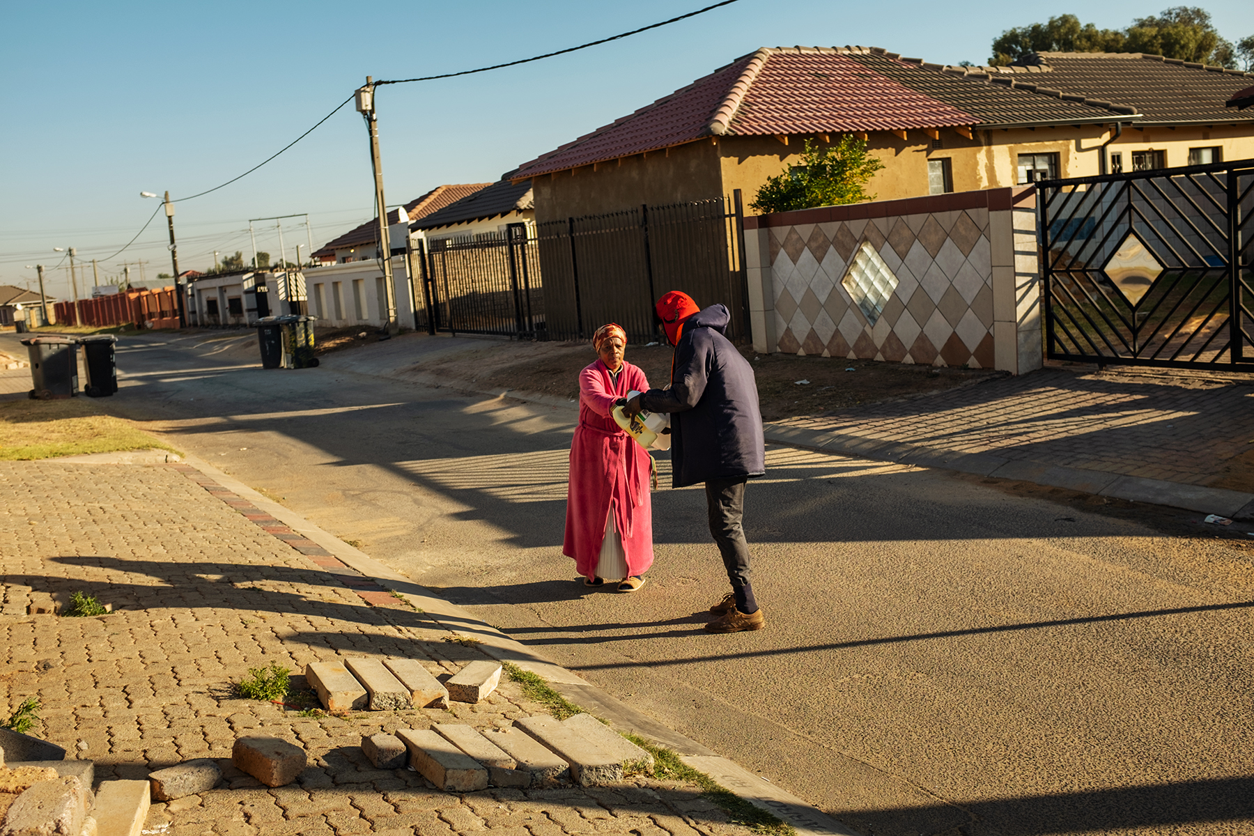 Scelo Sithole, 38, receives waste from a resident in Johannebsurg, South Africa, in the early morning of June 12, 2019.