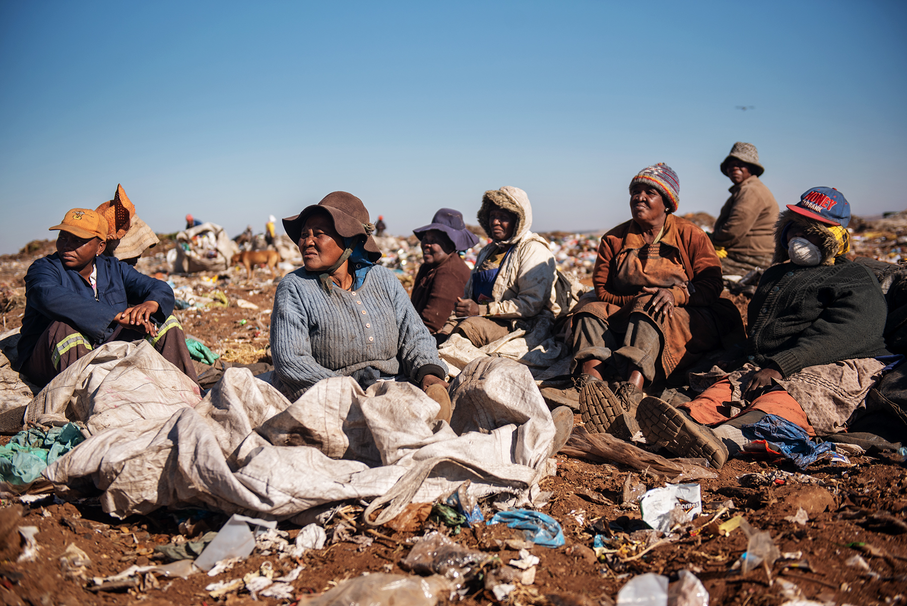 Maria Makoena (2-L), a 69 years old South African informal waste picker and mother of informal waste picker Eva Mokoena, rests along other informal recyclers at the Palm Springs landfill in the outskirt of Johannesburg, South Africa, on June 28, 2019.