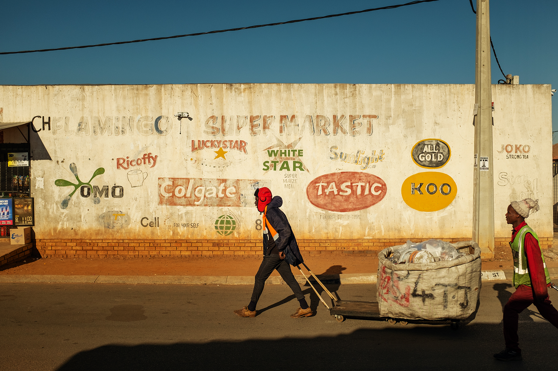 Scelo Sithole, 38, and Tumelo Ikaneng, 21, carry their trolleys filled with waste collected from trash bins in Johannebsurg, South Africa in the early morning of June 12, 2019.