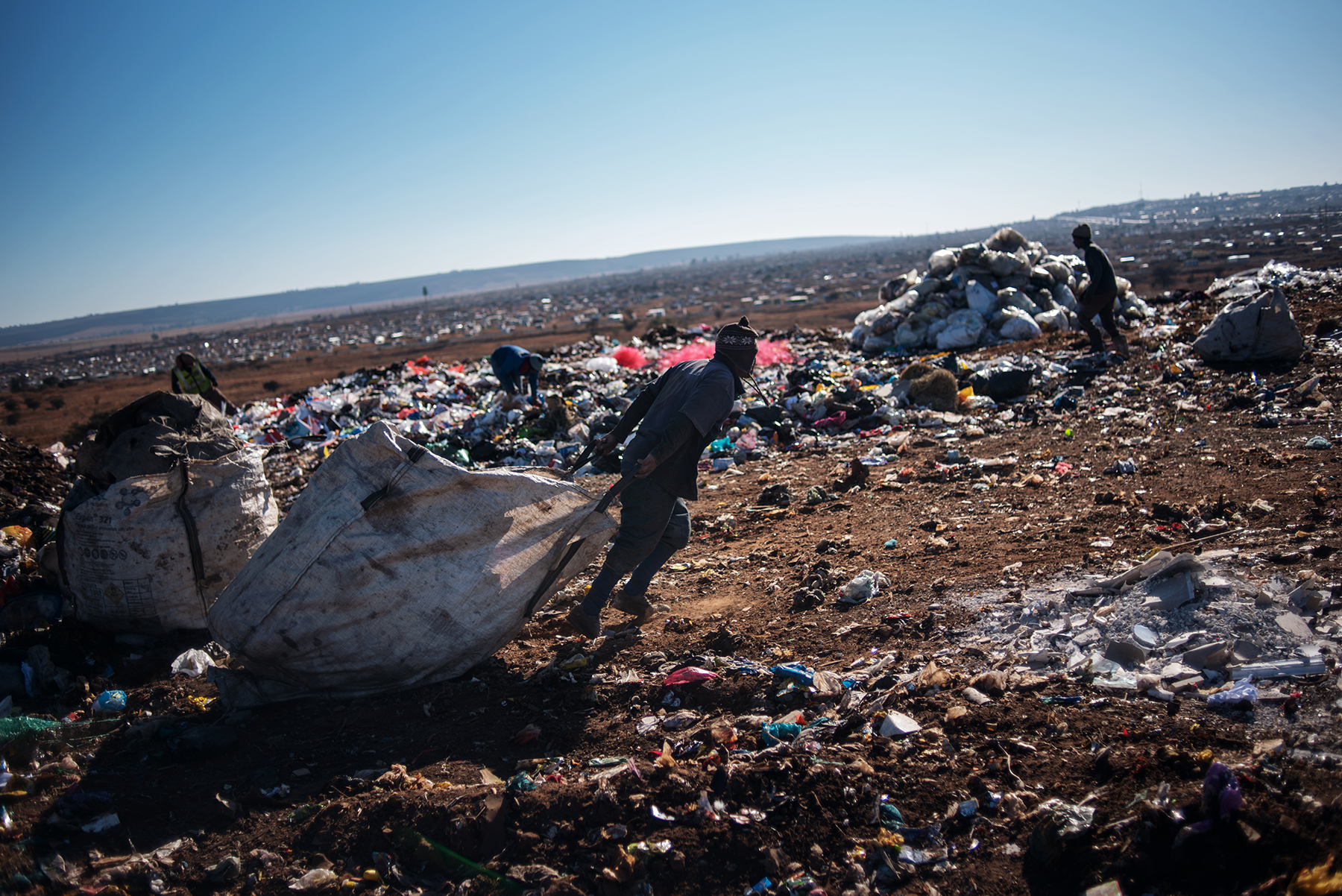An informal waste picker drags a sack filled up of waste dumped by a garbage truck at the Palm Springs landfill in the outskirt of Johannesburg, South Africa, on June 28, 2019.