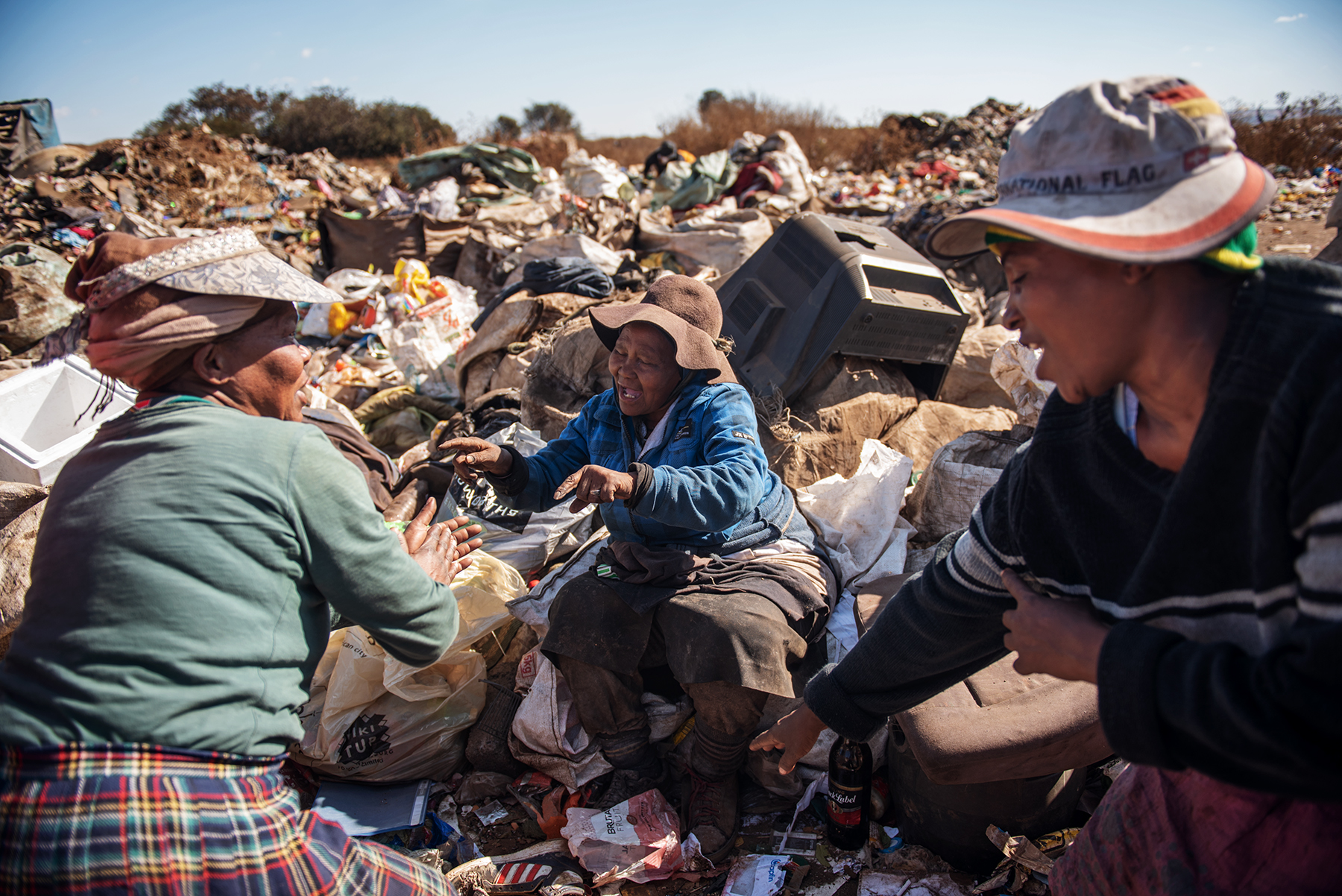 Malerato Mphuthi (L), Maria Makoena (C) and an other woman reclaimer dance surrounded by sacks filled up of waste at the Palm Springs landfill in the outskirt of Johannesburg, South Africa, on June 28, 2019.