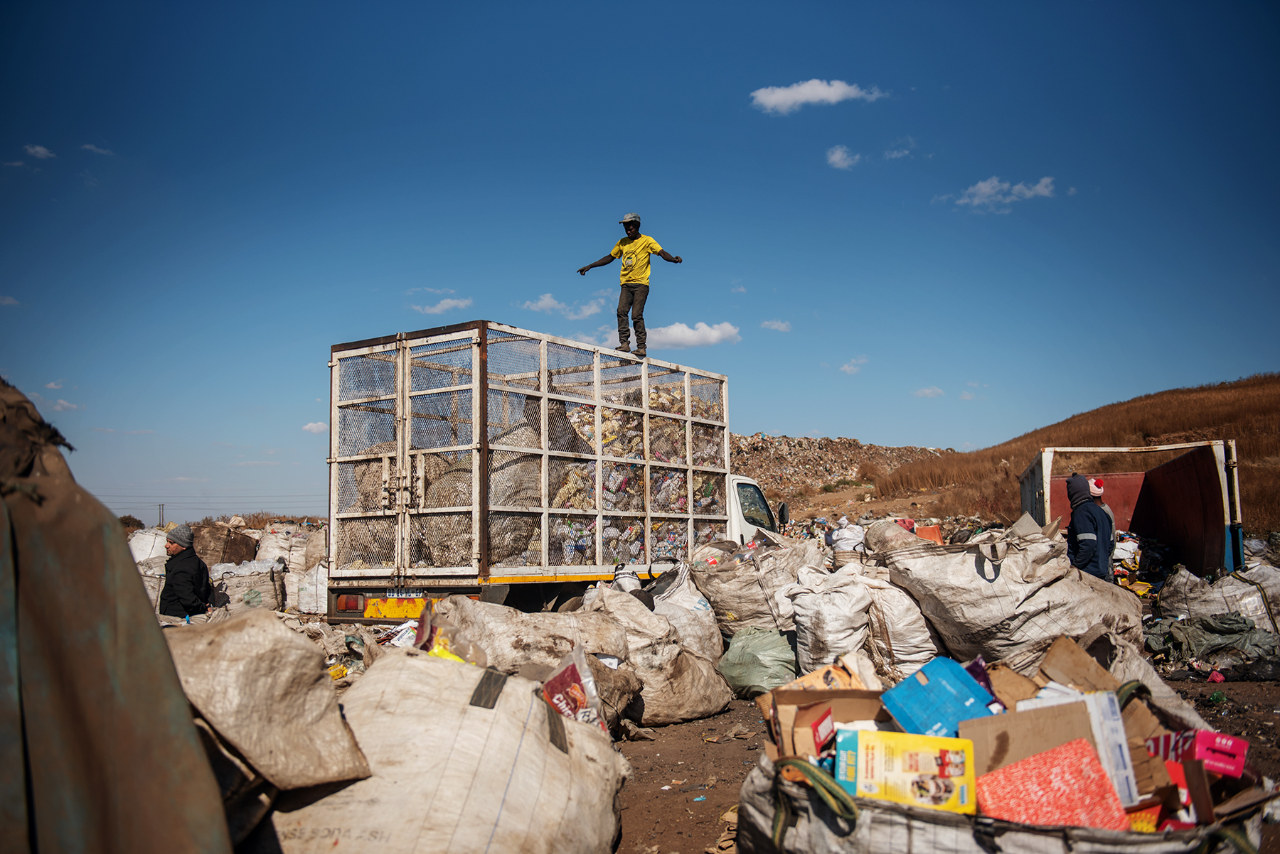 An informal waste picker walks on top of a garbage truck at the Palm Springs landfill in the outskirt of Johannesburg, South Africa, on June 28, 2019.