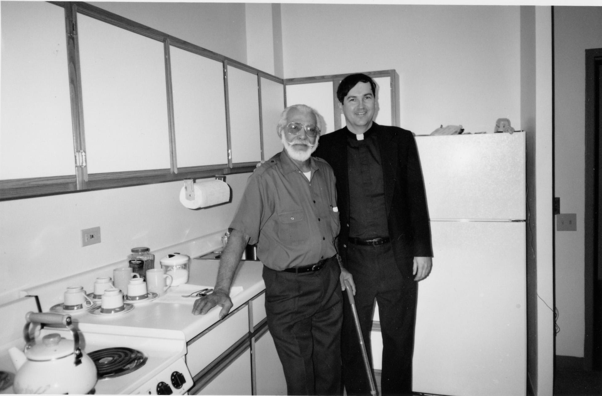 6-J   priest and senior in kitchen 70s.jpg