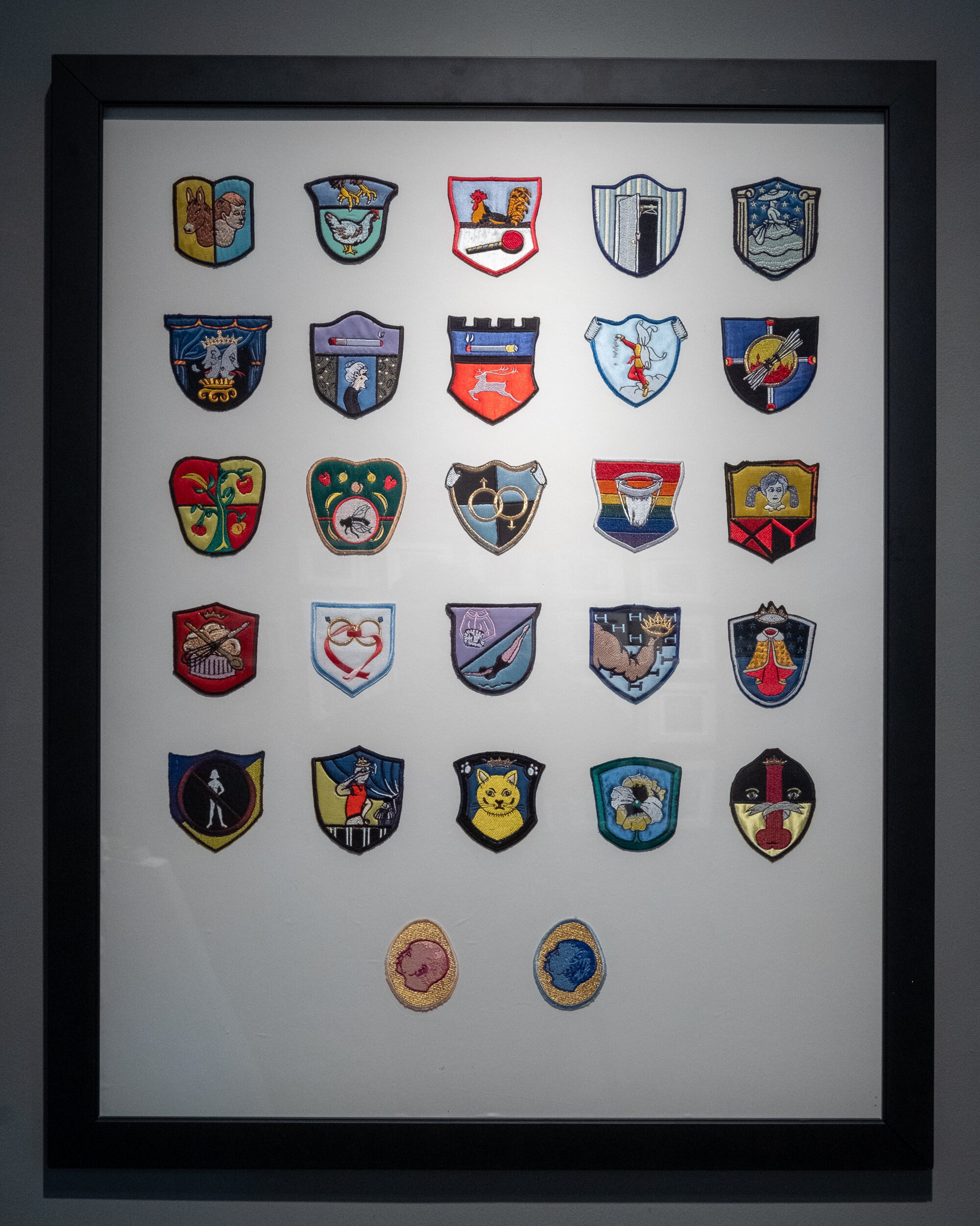18  Gay Merit Badges      framed group of gay merit badges produced in Italy 33 x 31.25 inches LJA 262G