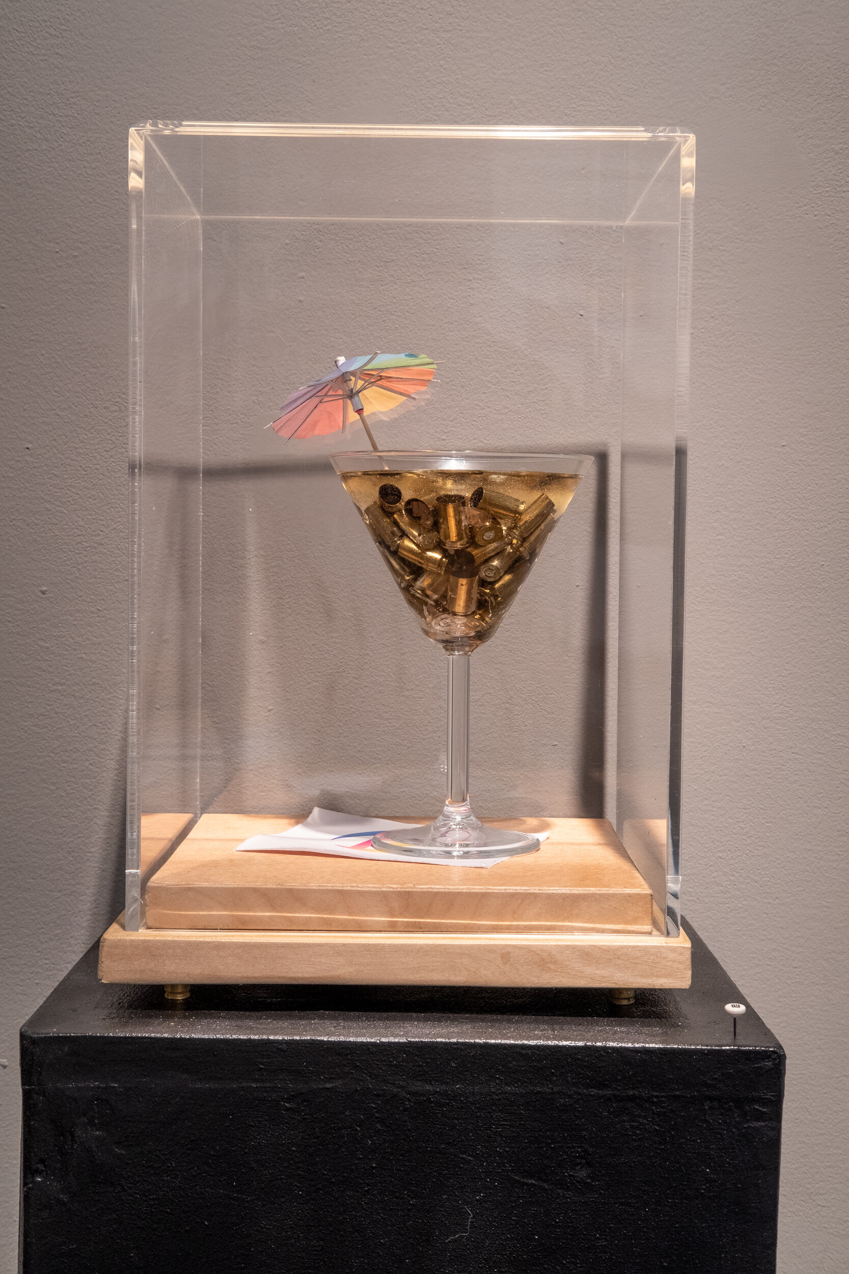 49 Cocktail      wooden base and plexi cover cocktail glass with 49 spent bullets (# of people who died in Pulse nightclub shooting), a rainbow colored cocktail umbrella, filled with clear resin standing on napkin with Pulse logo LJA 260G