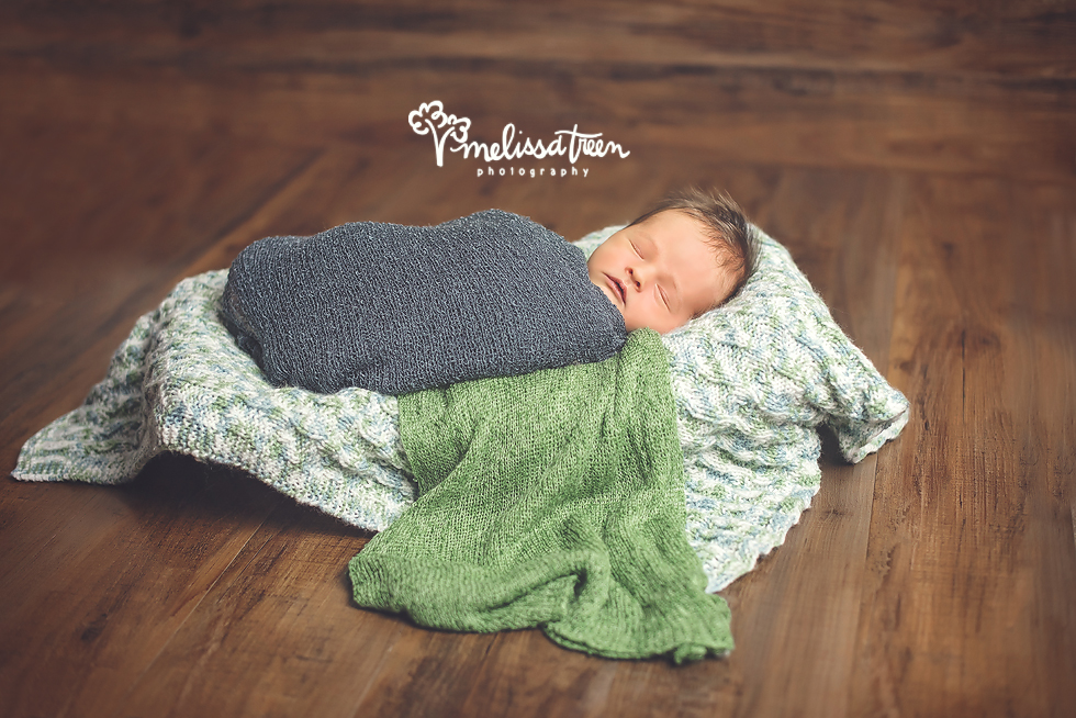 I am always eager to work in a treasured keepsake or heirloom into a portrait session, it makes for sweet memories.  Mom brought this gorgeous handmade baby blanket to her custom styled newborn photo shoot.  When I saw it, I instantly loved the colors and textures.  We played up the blues and greens in the blankie and it photographed so well.  This little guy was altogether precious throughout his newborn portrait session in our West Burlington portrait studio.  He snuggled into sleepy time and we captured beautiful images.