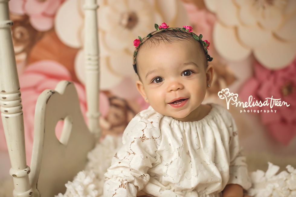 When this sweet baby girl arrived at the studio for her first birthday photo shoot, she was all smiles. I knew then this birthday portrait session would be amazing and it did bot disappoint. We styled the scene with all things girly, pink and cream flowers, a pink halo, creamy white canopy bed and mom dressed her in this gorgeous lace romper ... how perfect does it get!