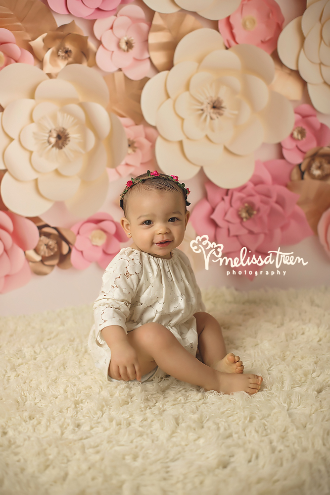 she had smiles for days during her first birthday photo shoot and cake smash, stlyed with pink and cream rosettes