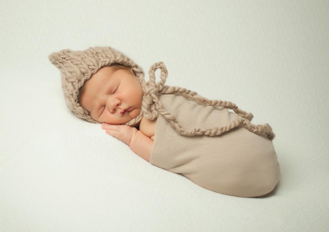 newborn photography hihg point north carolina sleeping baby in bonnet on cream blanket .jpg