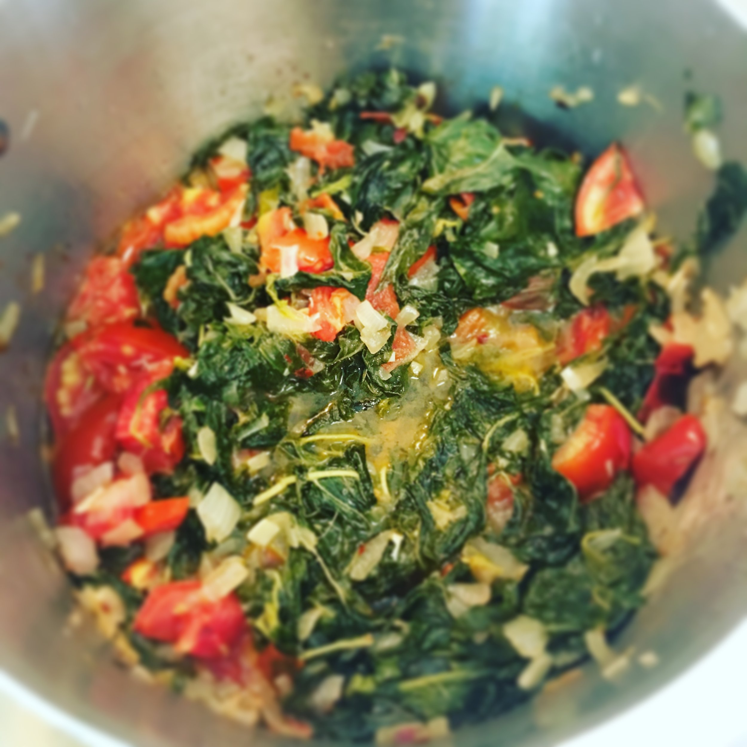 Spinach is cooked with onions, garlic, tomatoes, red pepper flakes, salt and pepper.