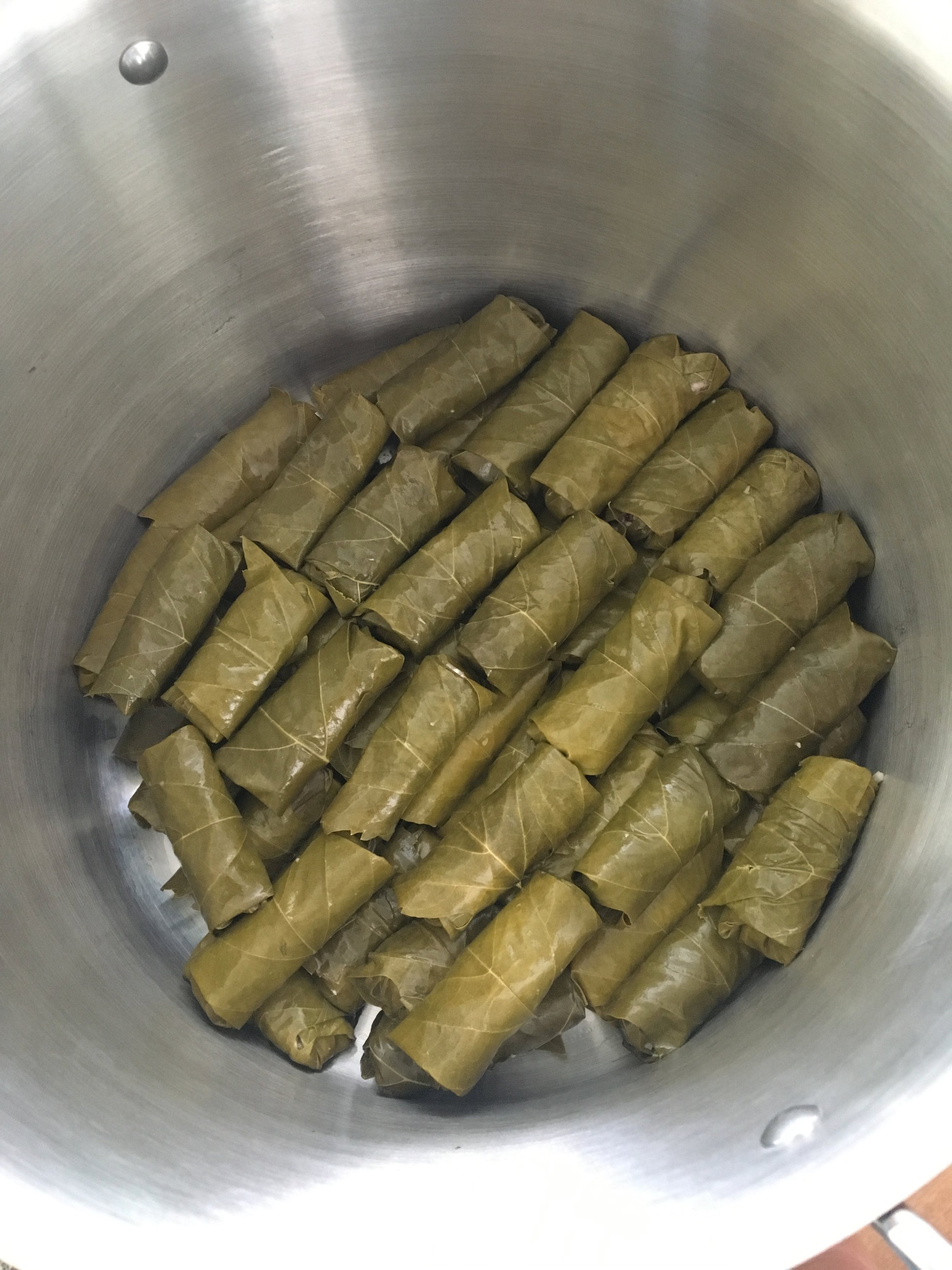 Double layer of dolmas in the pot, seam side down so the simmering doesn't cause them to unroll.