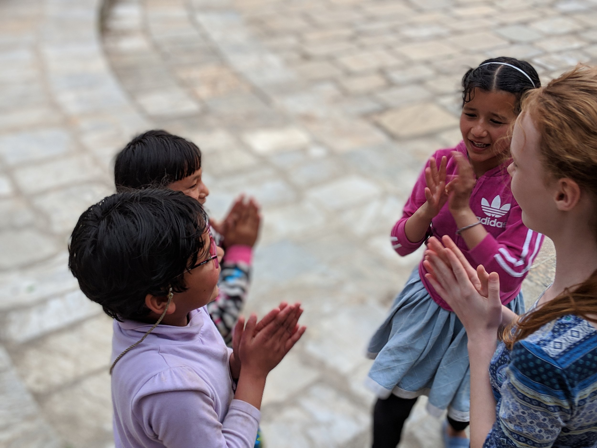My daughter, Lila, plays a clapping game with a group of girls at Ama Ghar, a children's care home in the Kathmandu valley in Nepal.