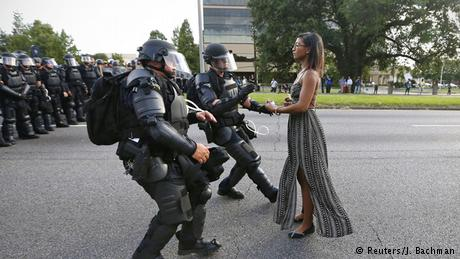 Lone black woman in flats and maxi dress approached by armored cops. Avengers and Suicide Squad just out of the frame. (Reuters/J. Bachman)