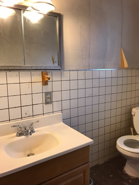 Before: Bathroom with old tile and chipping floor.