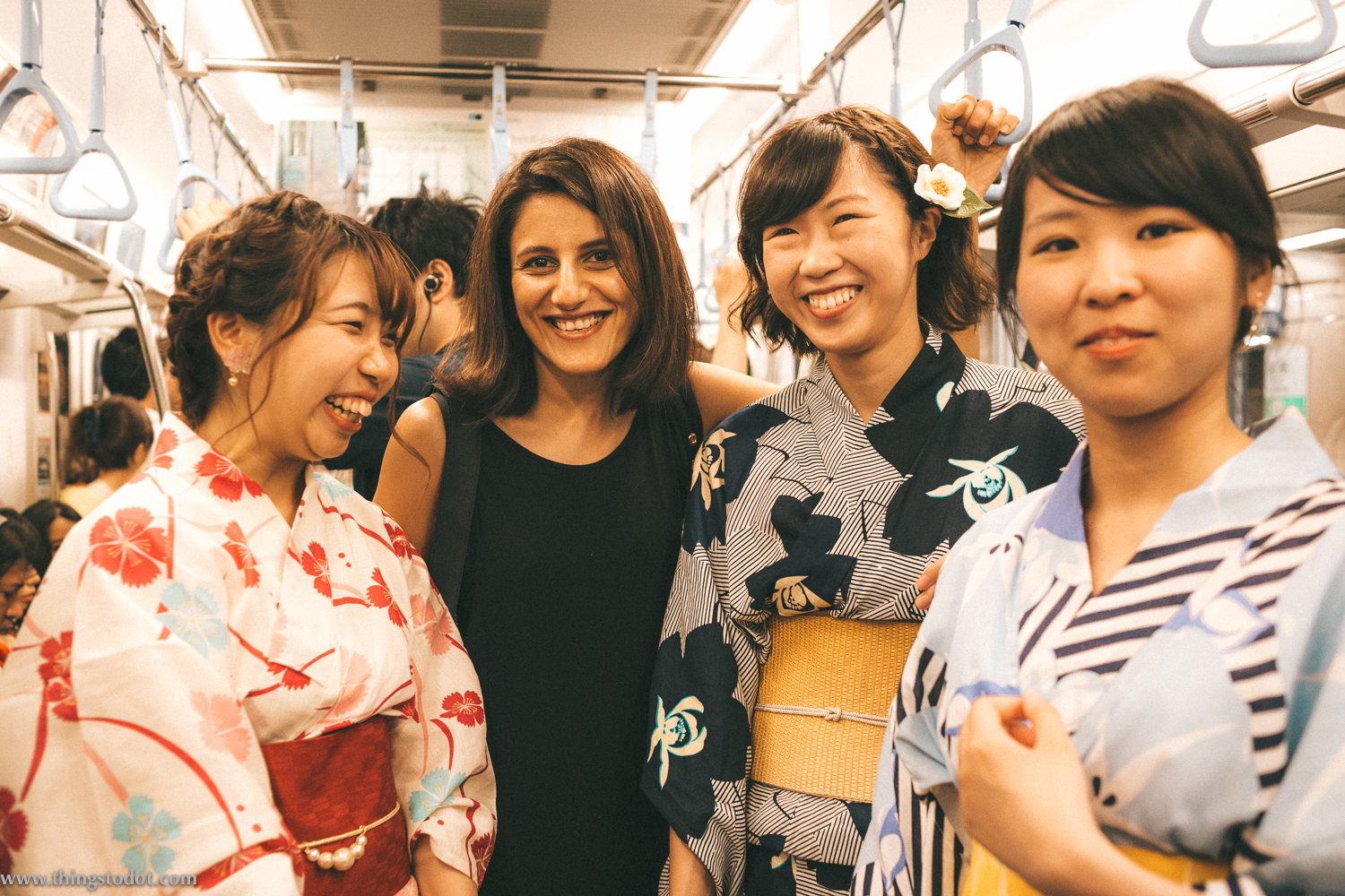 With Japanese girls in traditional clothing, in metro to the Adachi Fireworks on Arakawa river, Tokyo, Japan. Image©www.thingstodot.com.