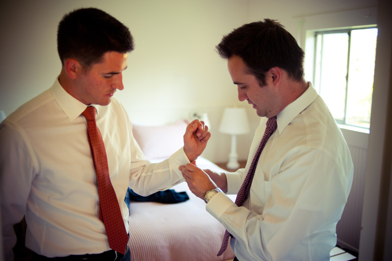 Brother helping groom get ready in Anchor Bay, CA