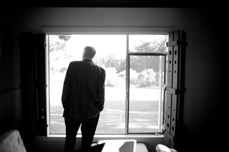 Father of bride looking out window in Anchor Bay, CA