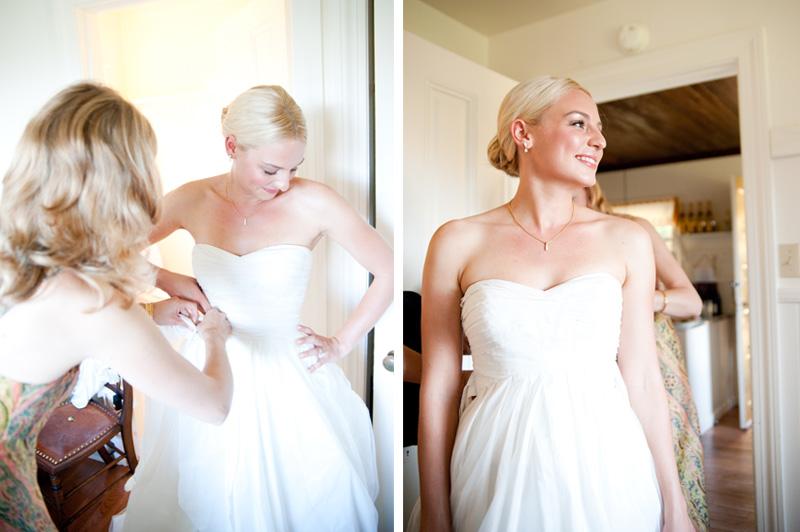 Bride getting into wedding dress inside cabin at Mar Vista Cottages